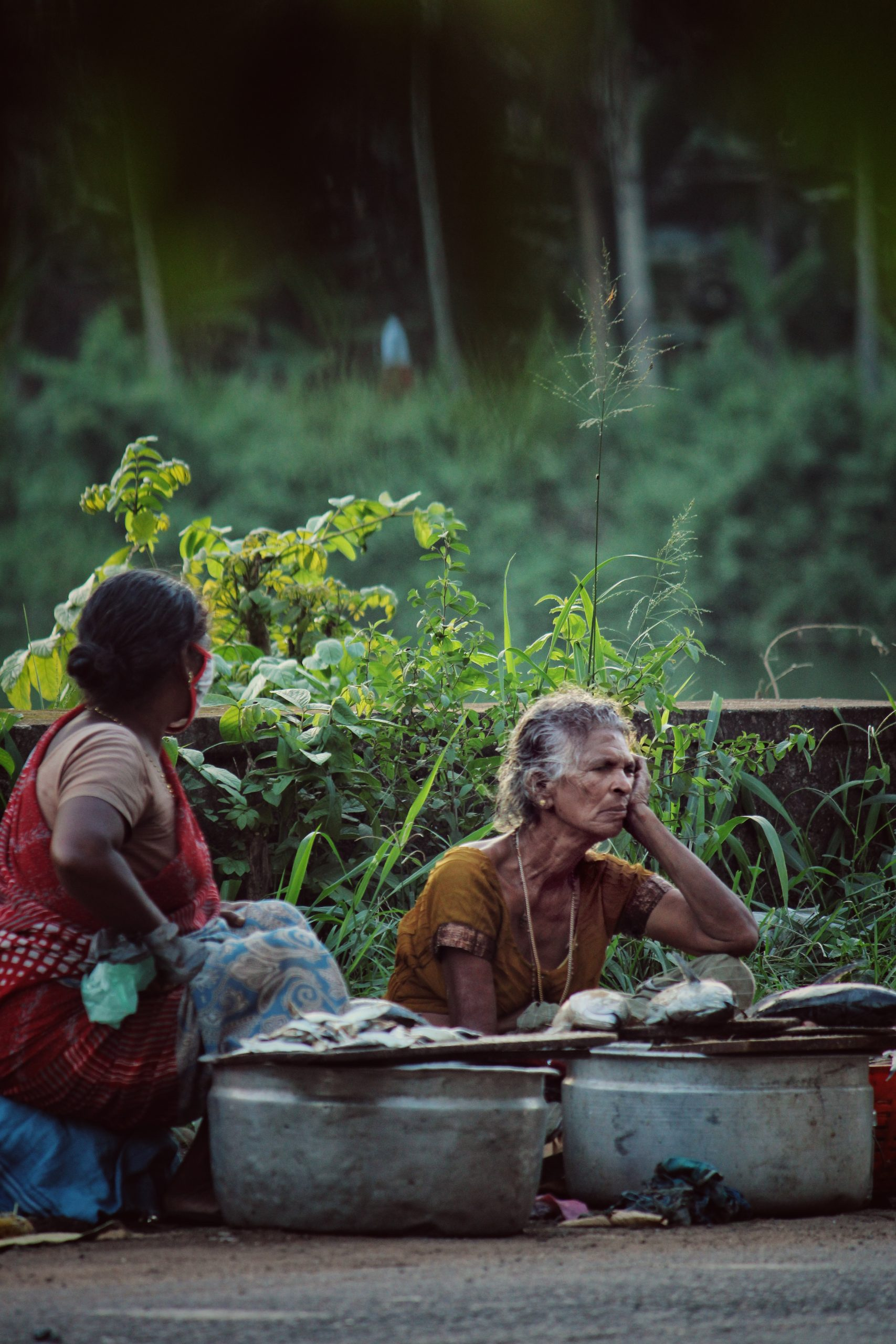 women selling fish on the road side