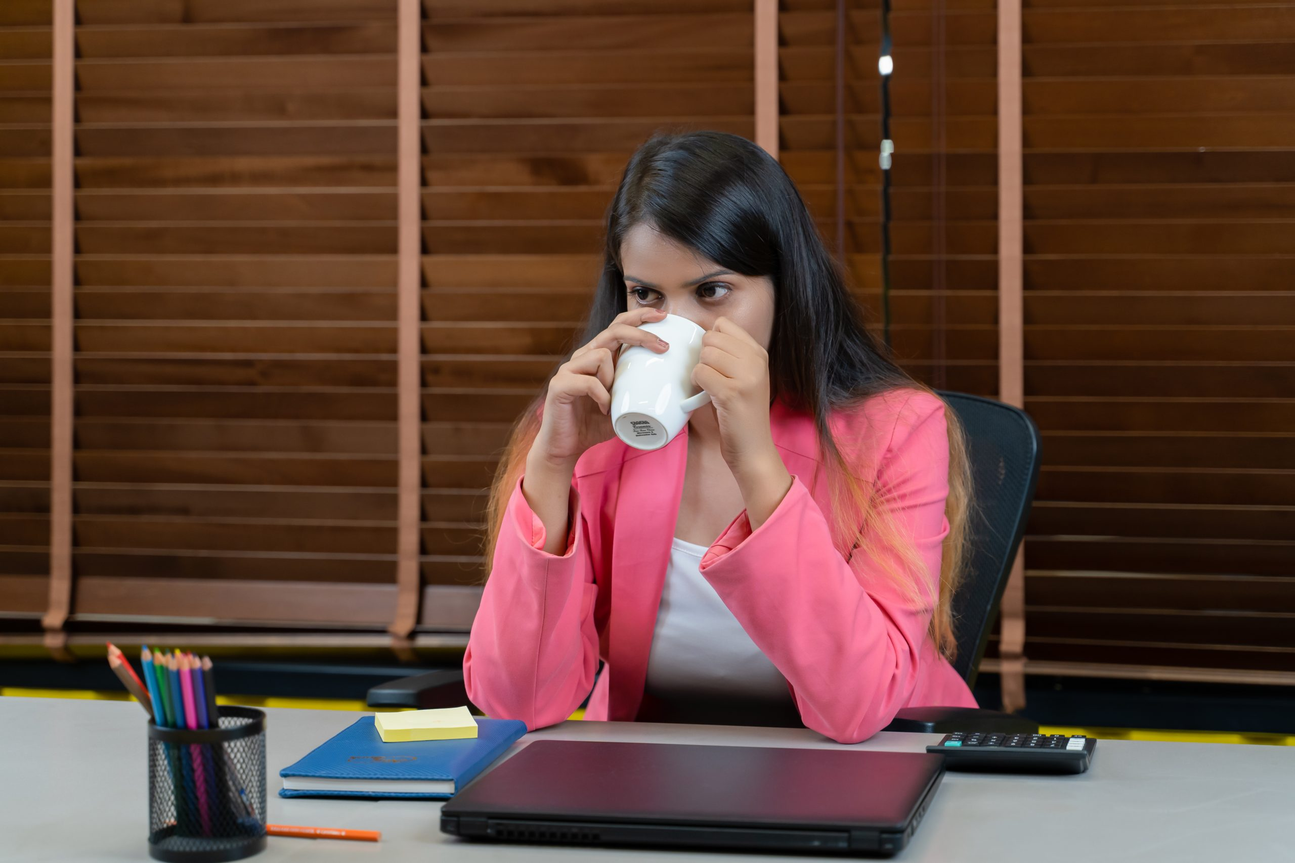Tired businesswoman drinking coffee.