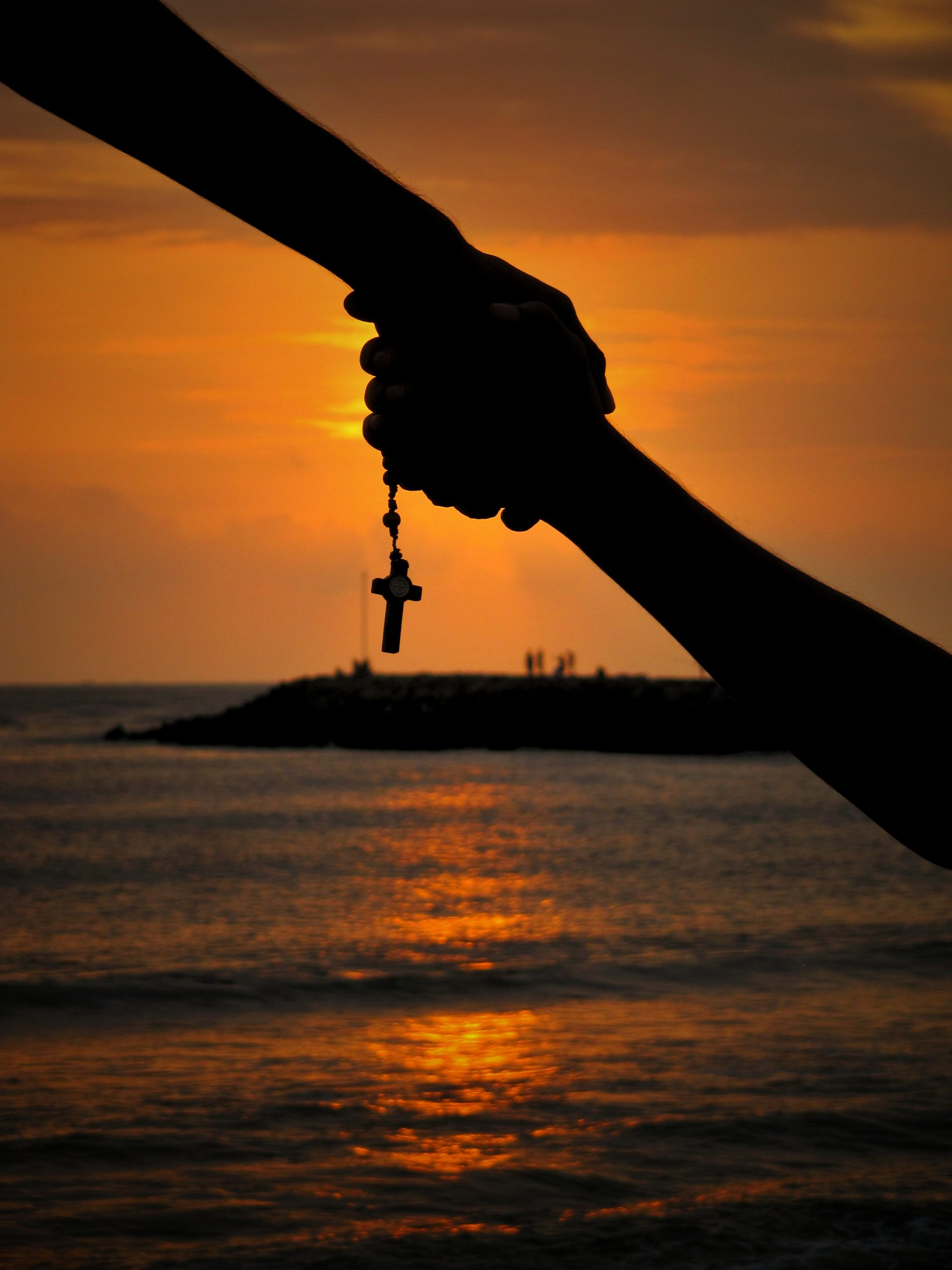 silhouette of holding hands at sunset