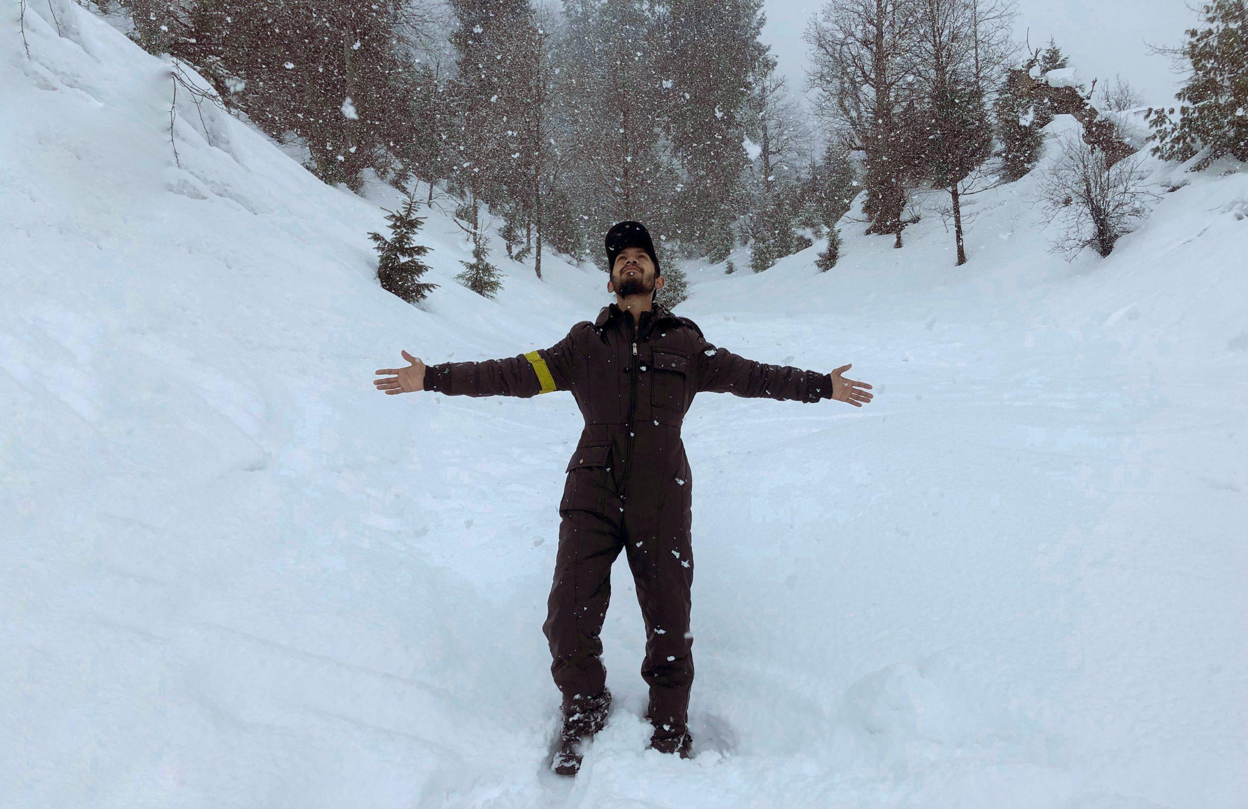 A man enjoying snowfall at the mountain.