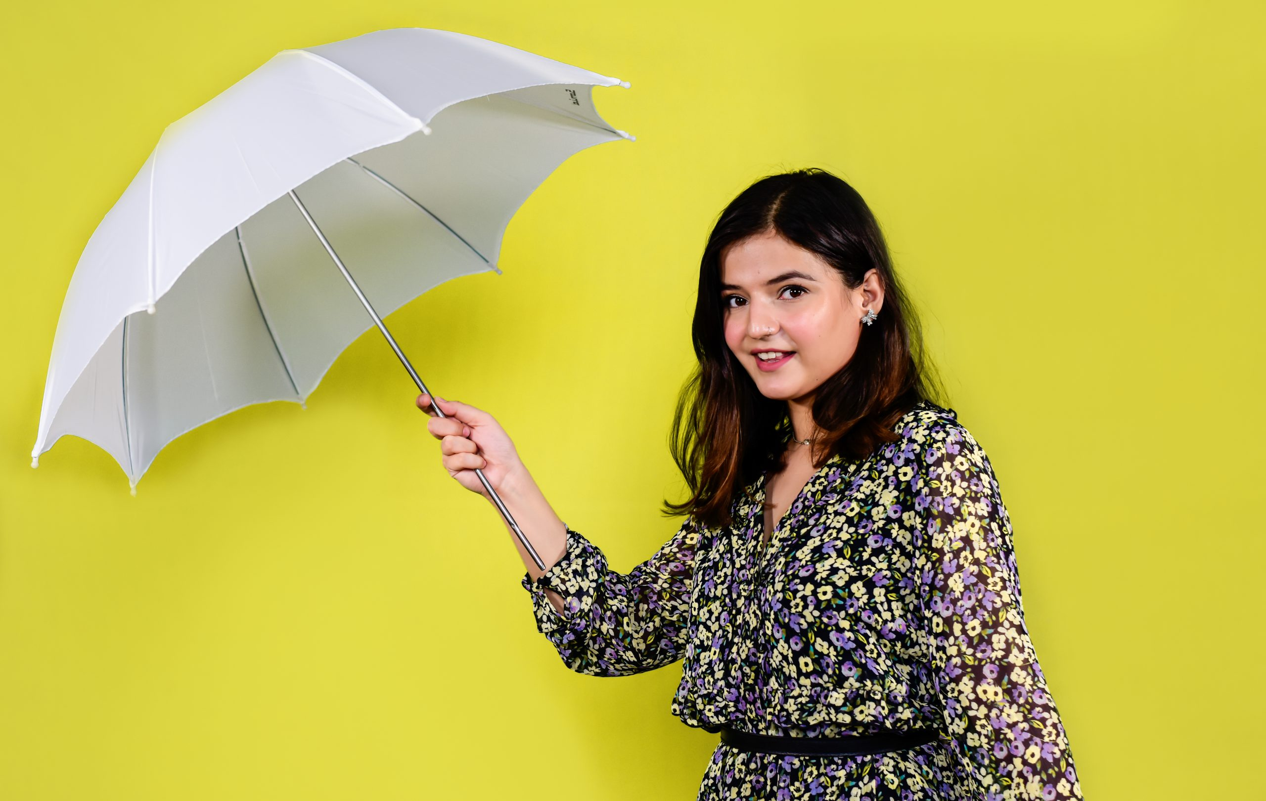 A model holding white umbrella for a photoshoot.