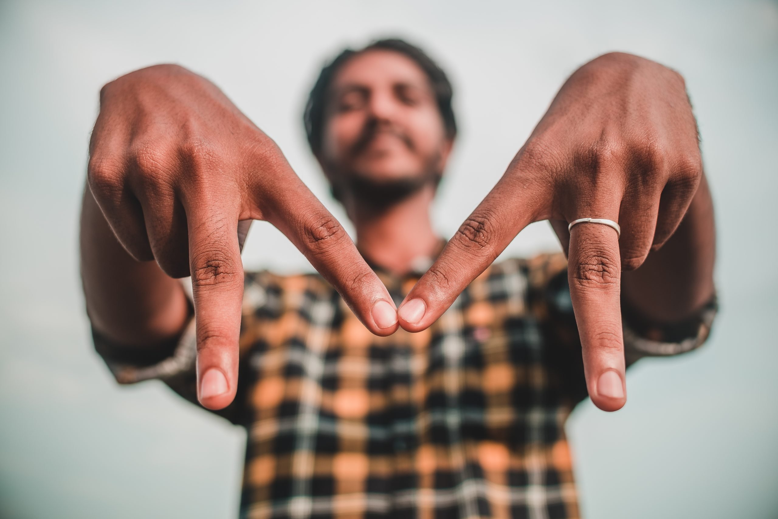 man making M with fingers
