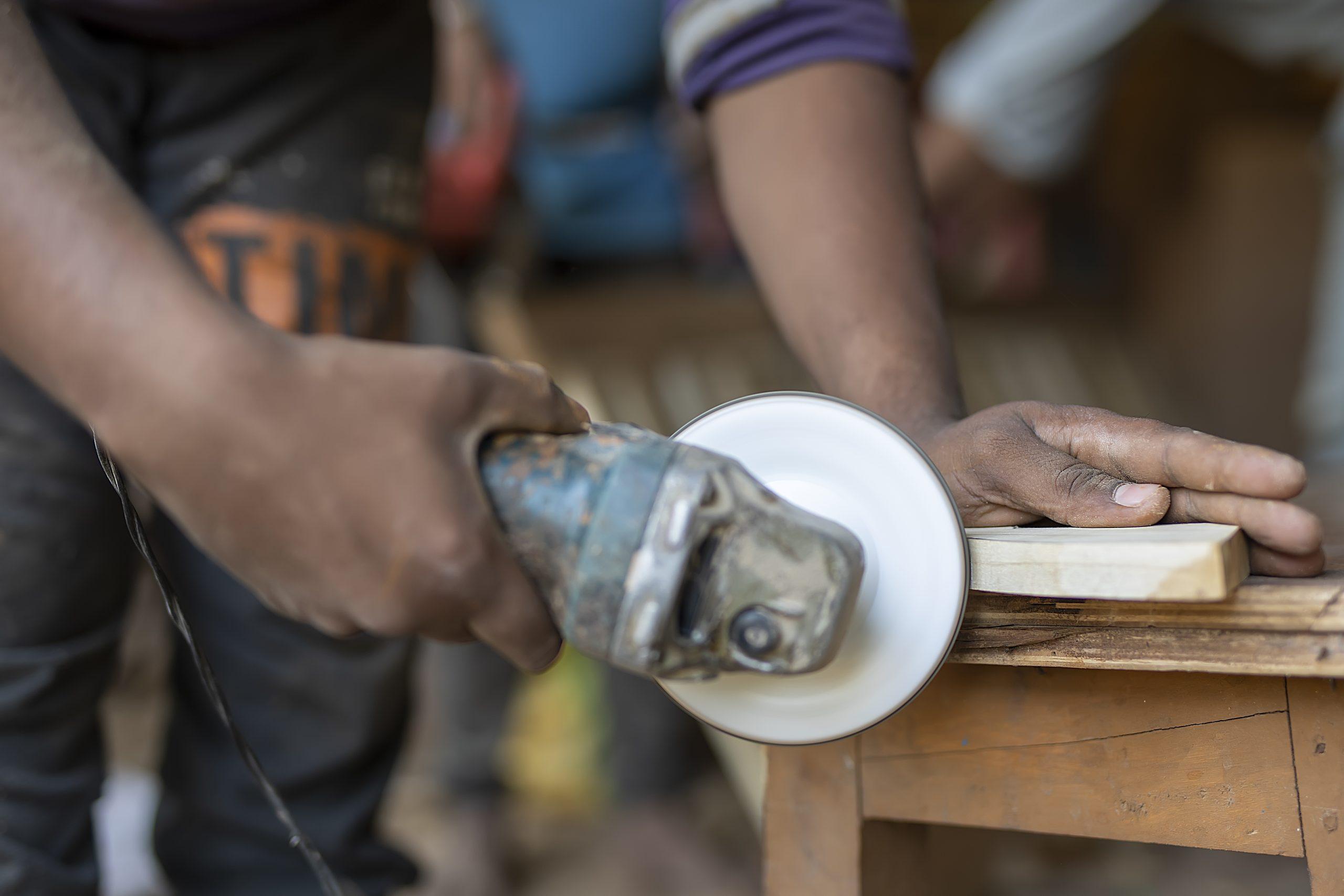 A carpenter cutting a wooden piece