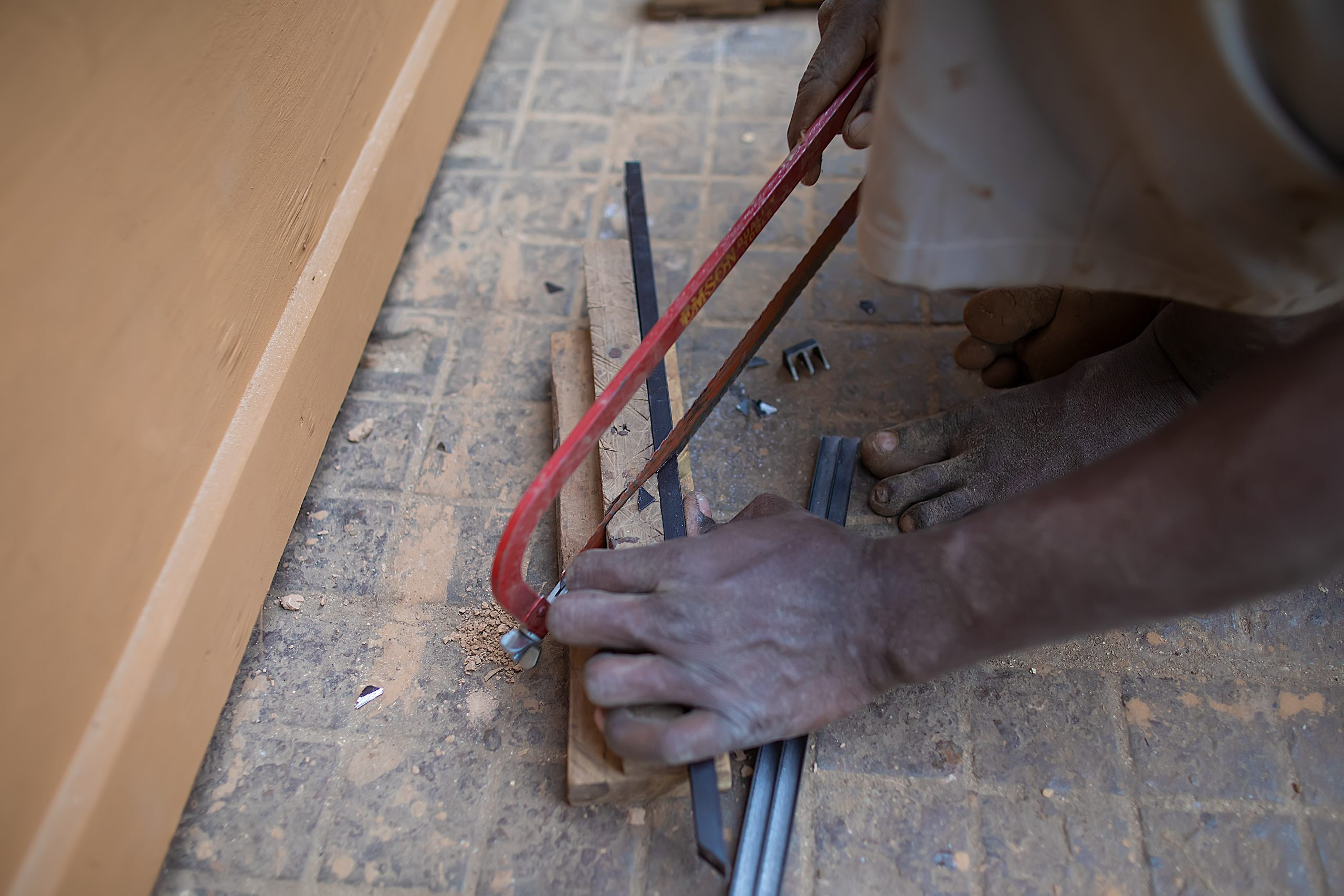 A carpenter cutting with hacksaw