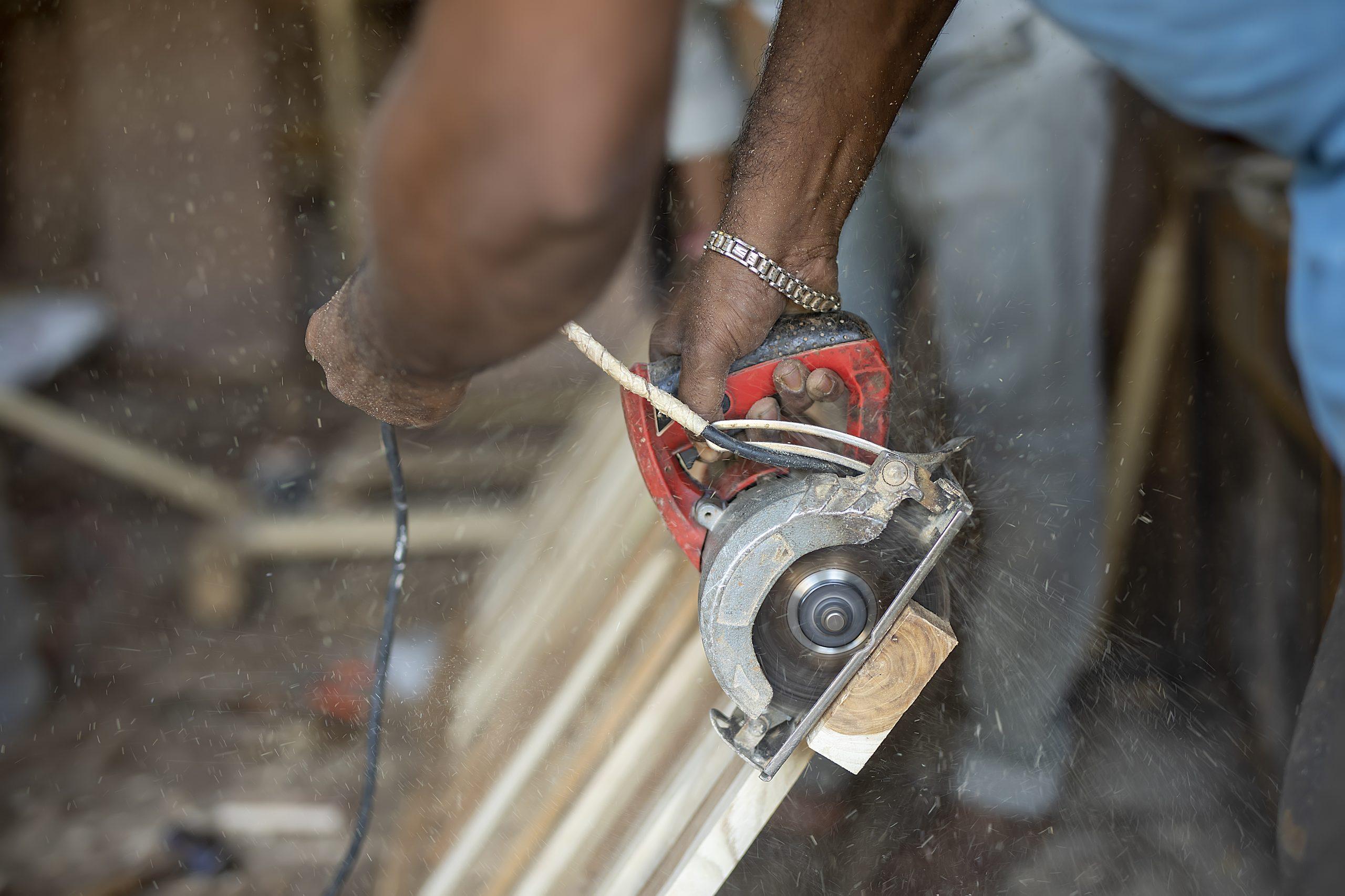 A carpenter cutting wood with a cutter