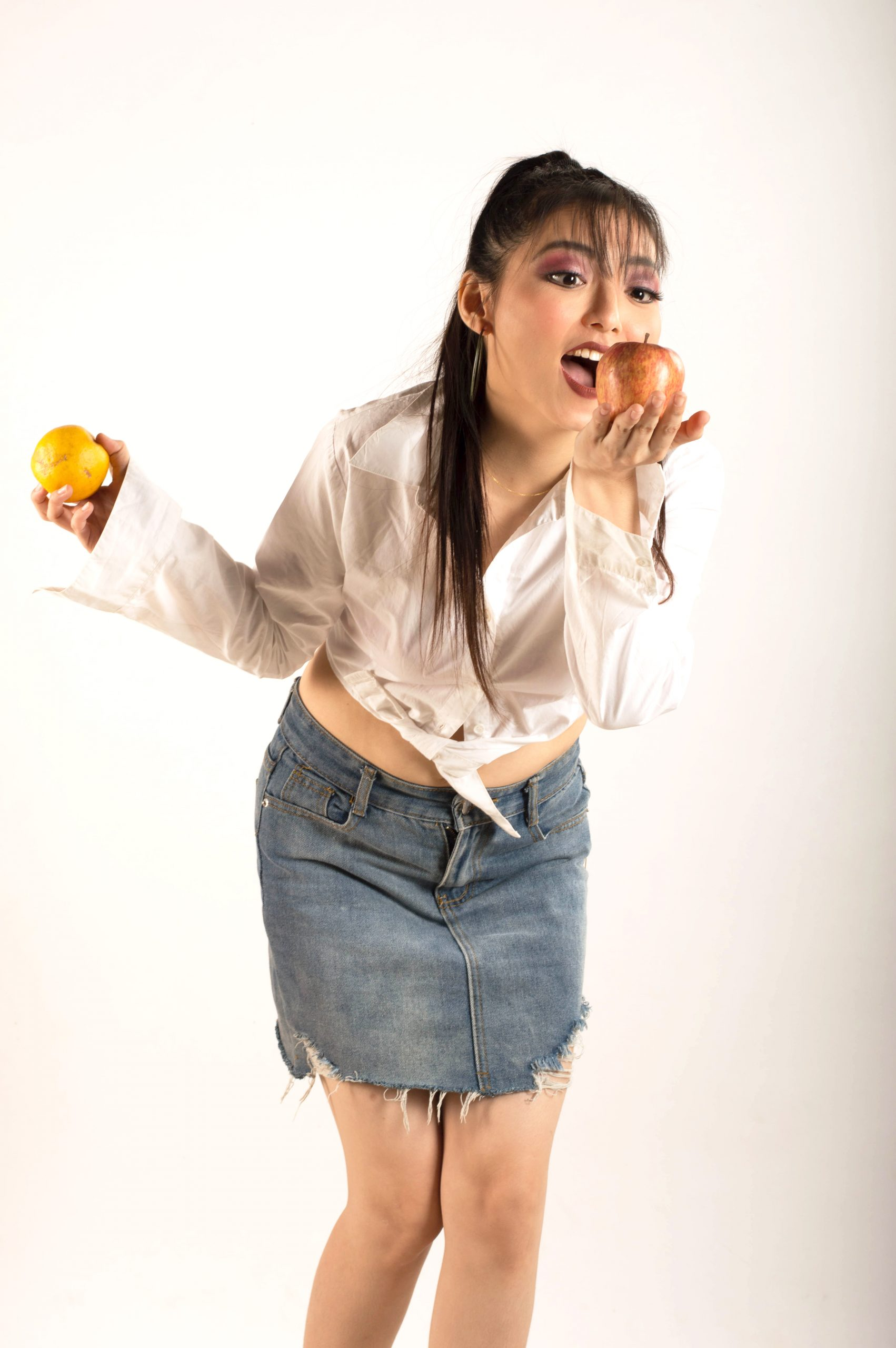 A fashion model eating an apple