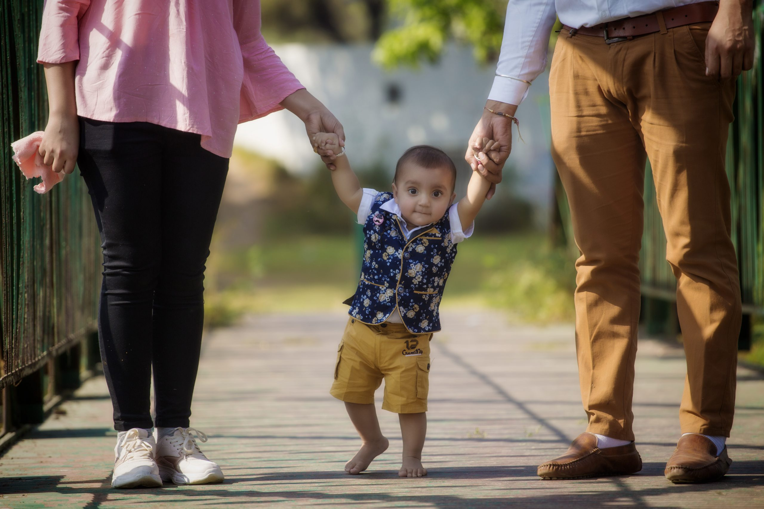 A little kid walking with parents