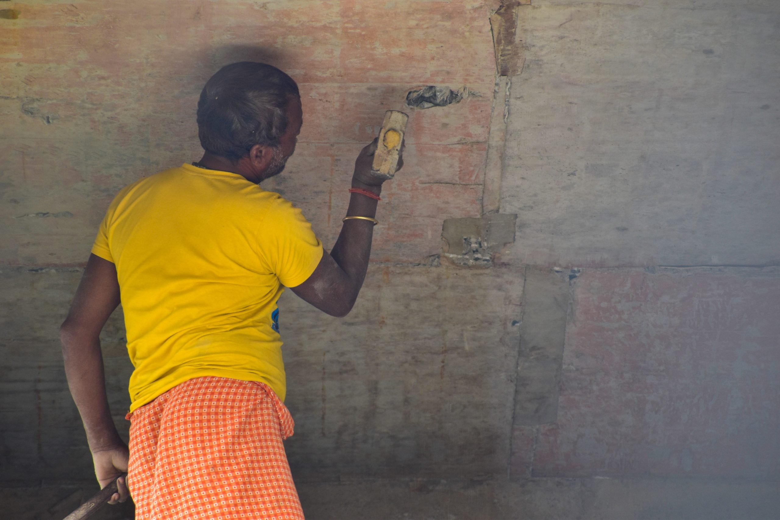 A man hammering on a wall
