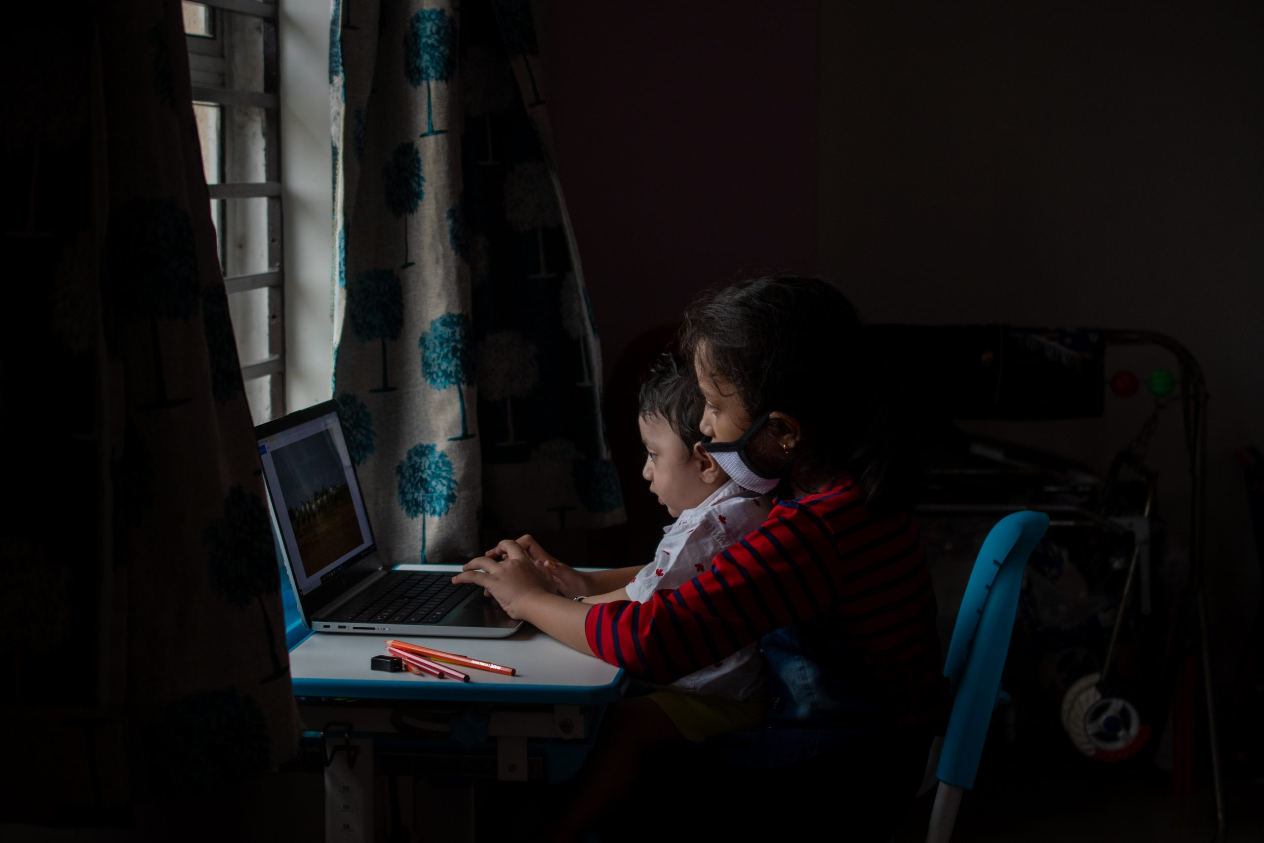 A mother teaching computer to a kid