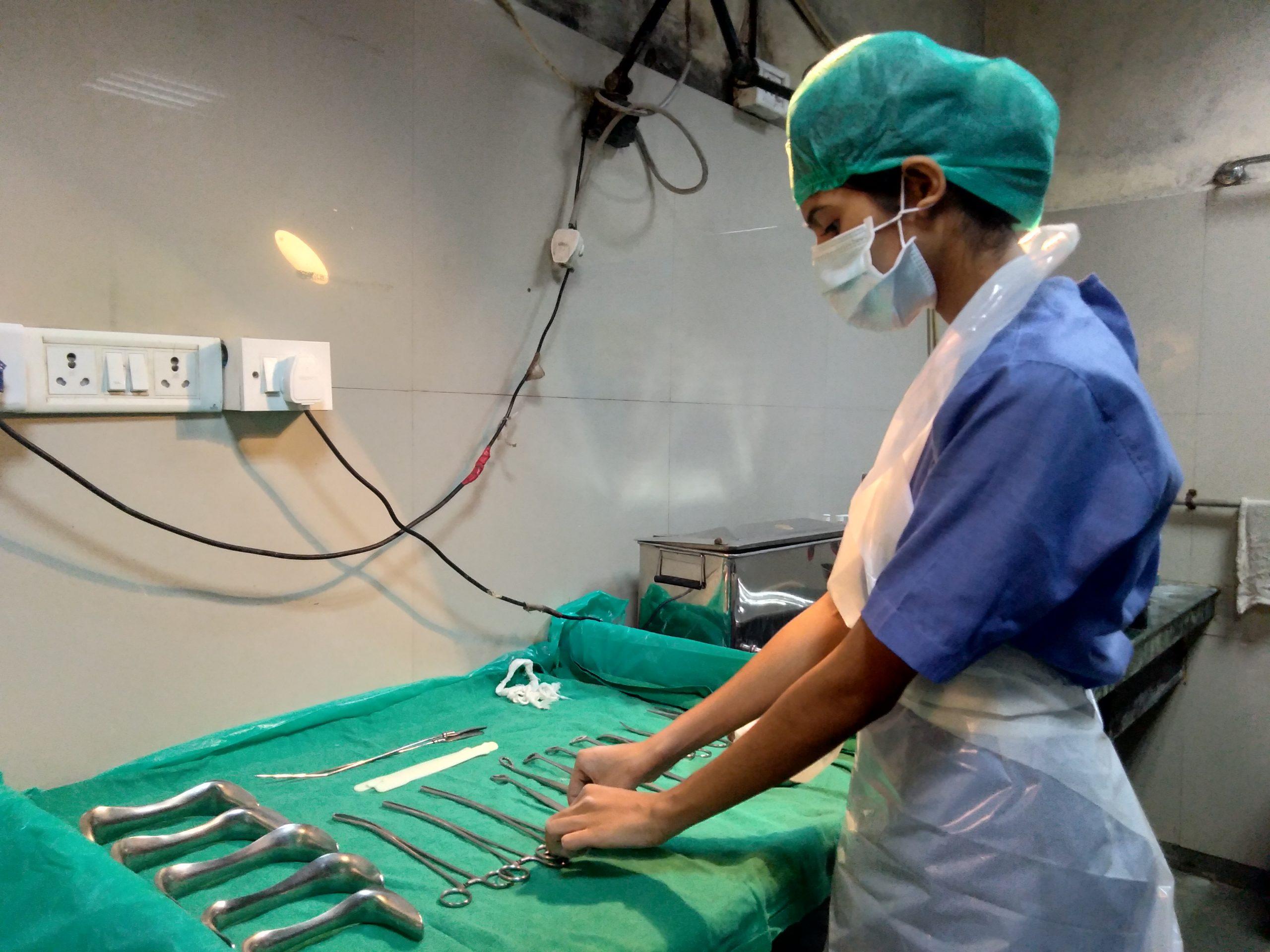 A nurse preparing tools in operation theatre