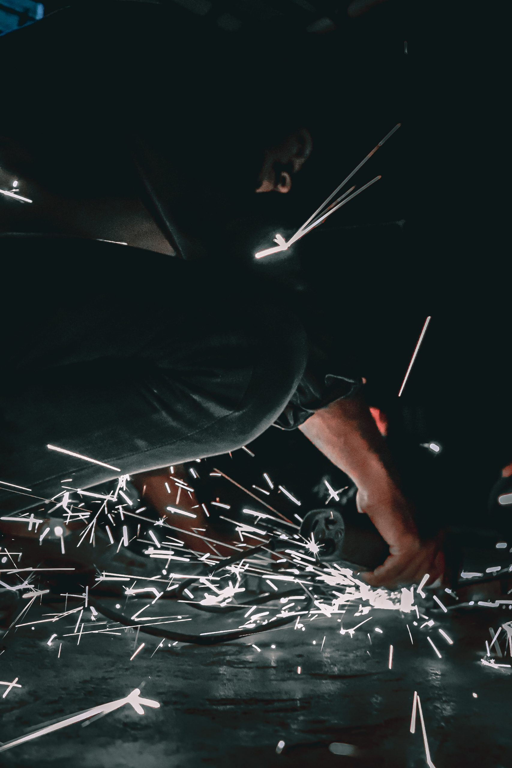 A technician cutting metal piece