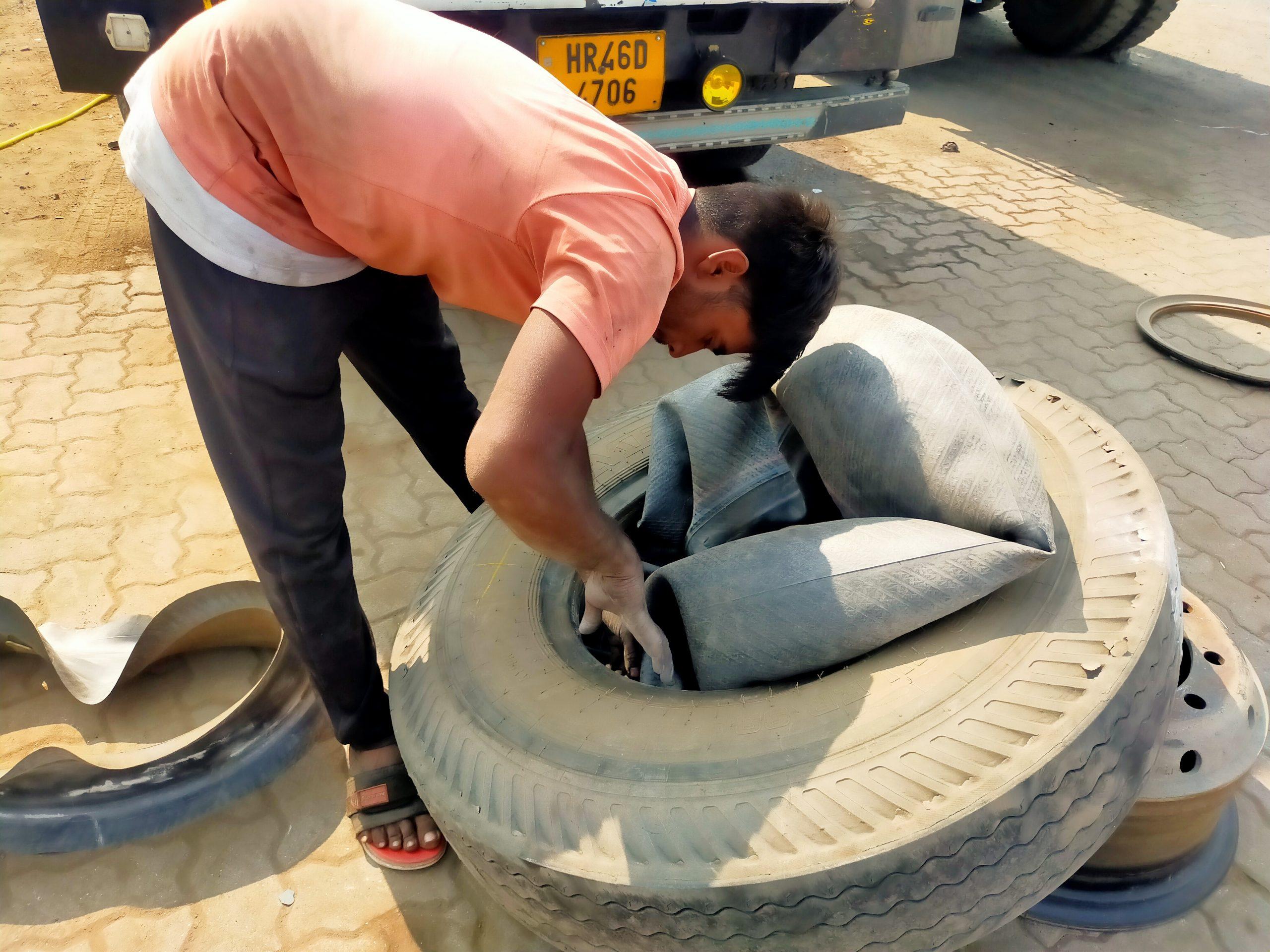 An auto mechanic repairing tyre tube