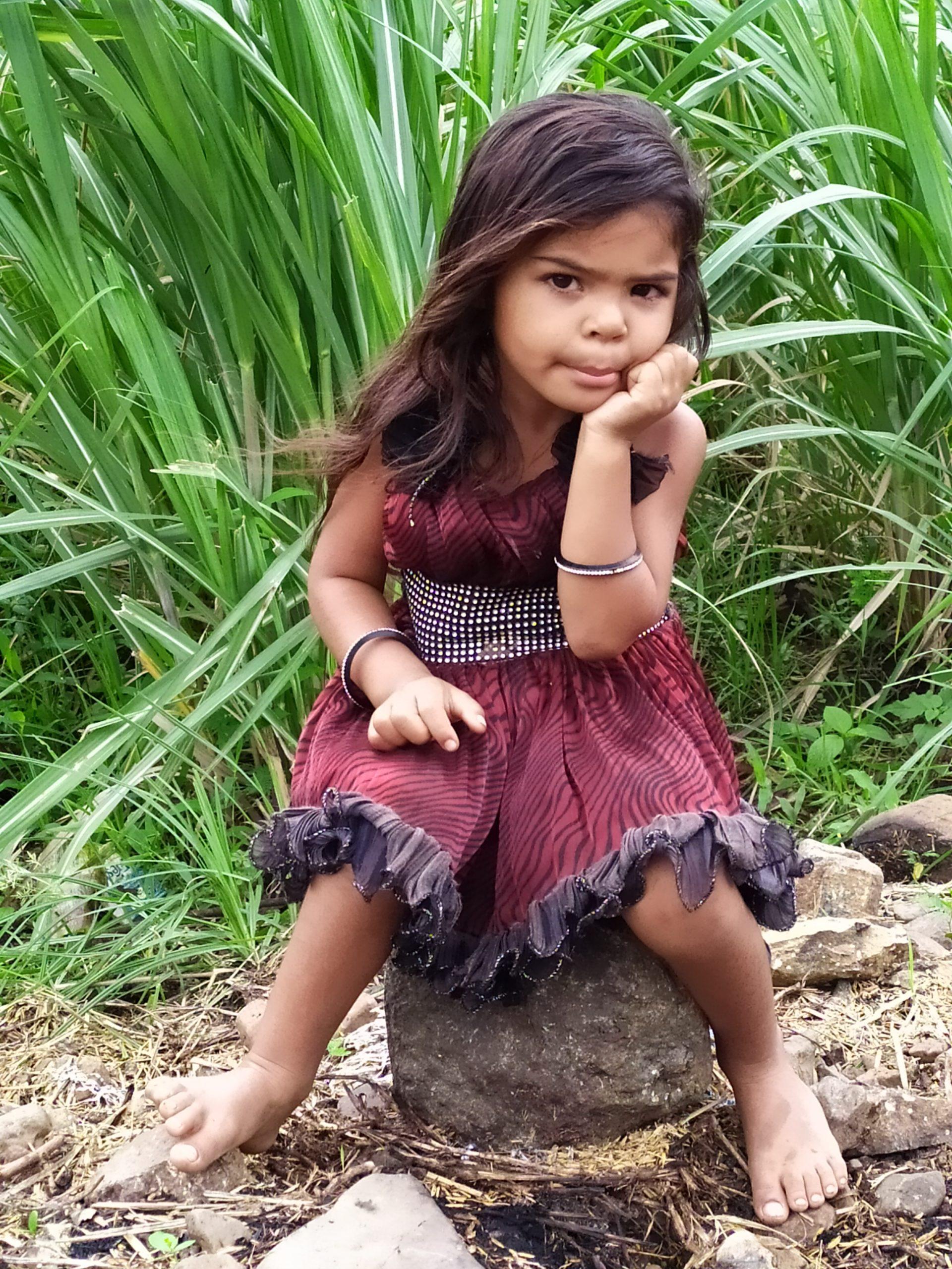 Girl Sitting on a rock in farm