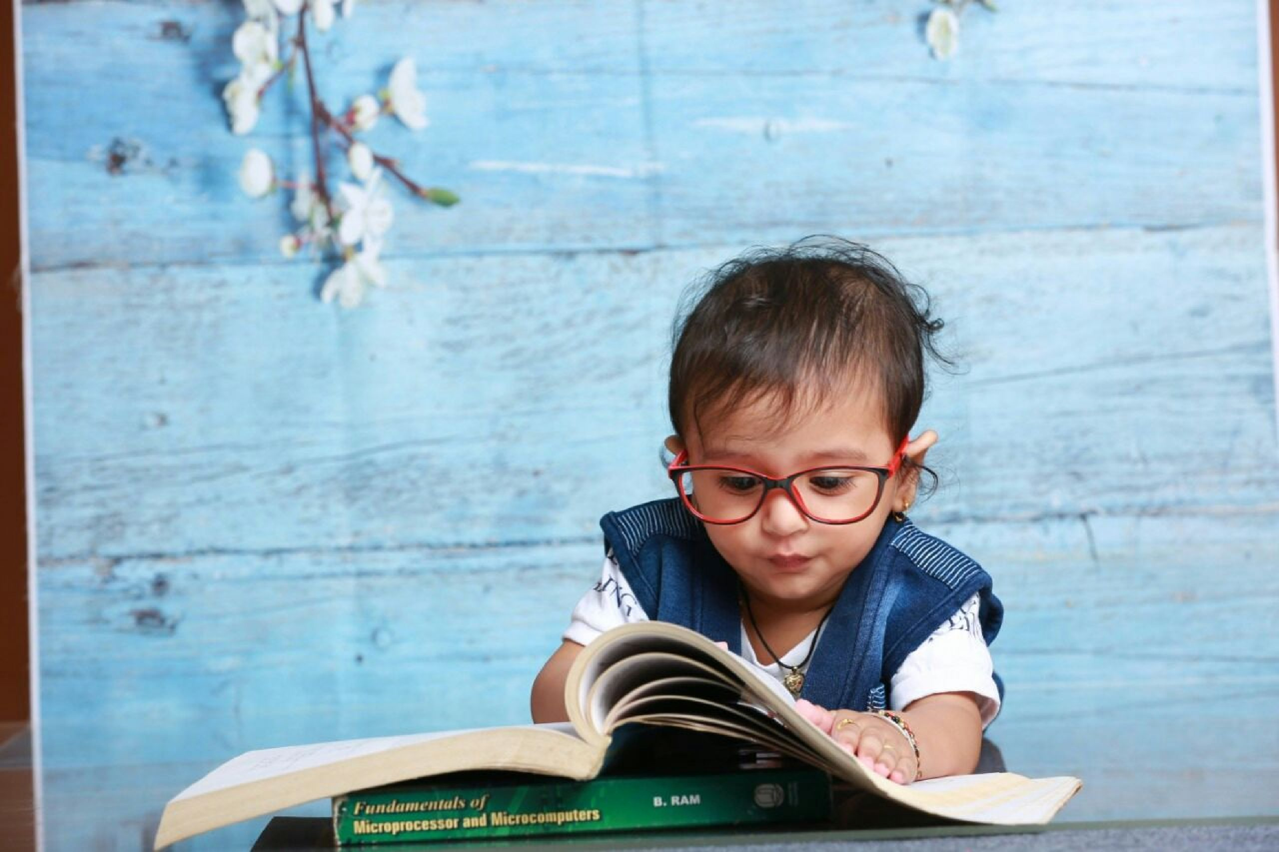 kid with spectacles reading book