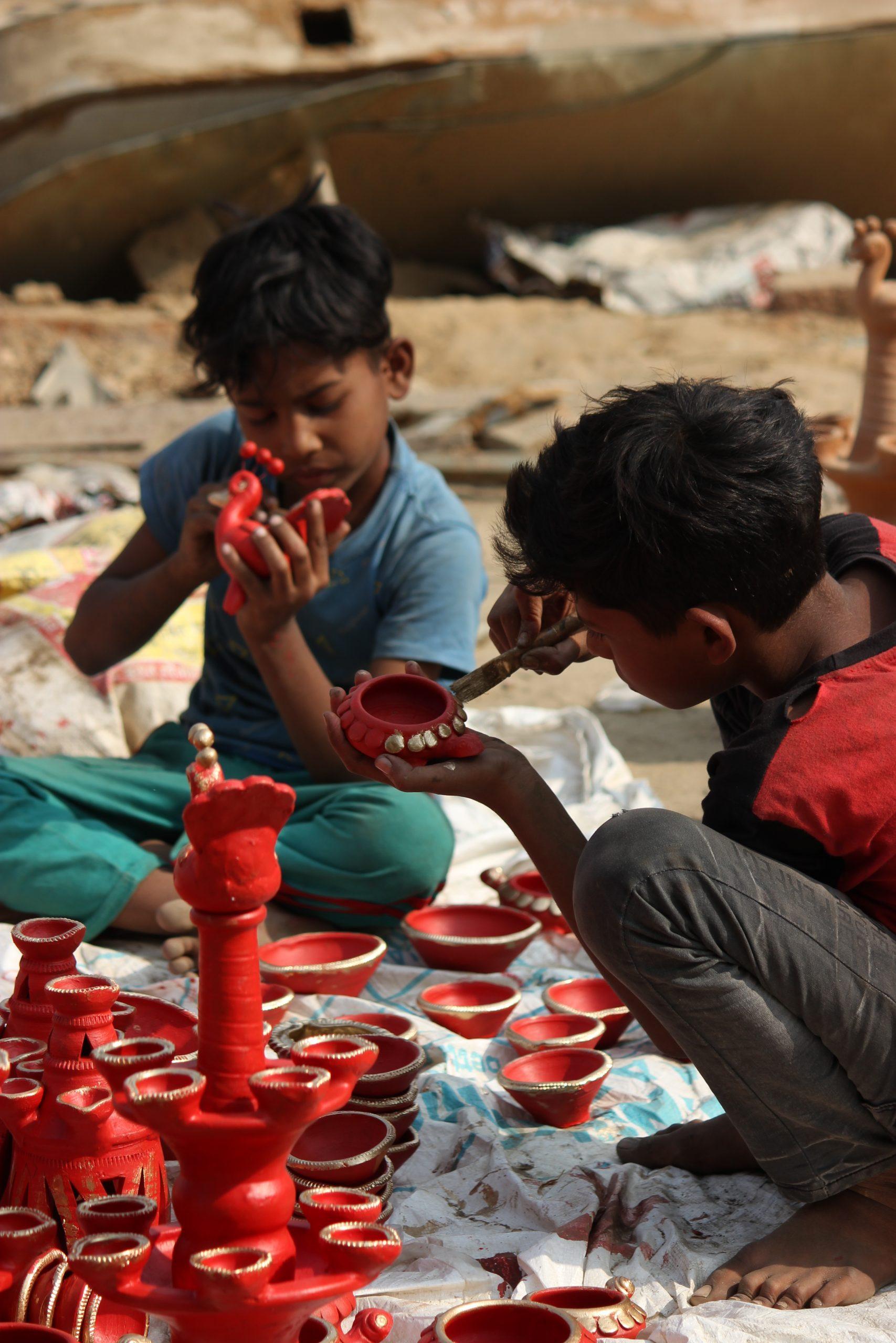 Boys designing clay pots