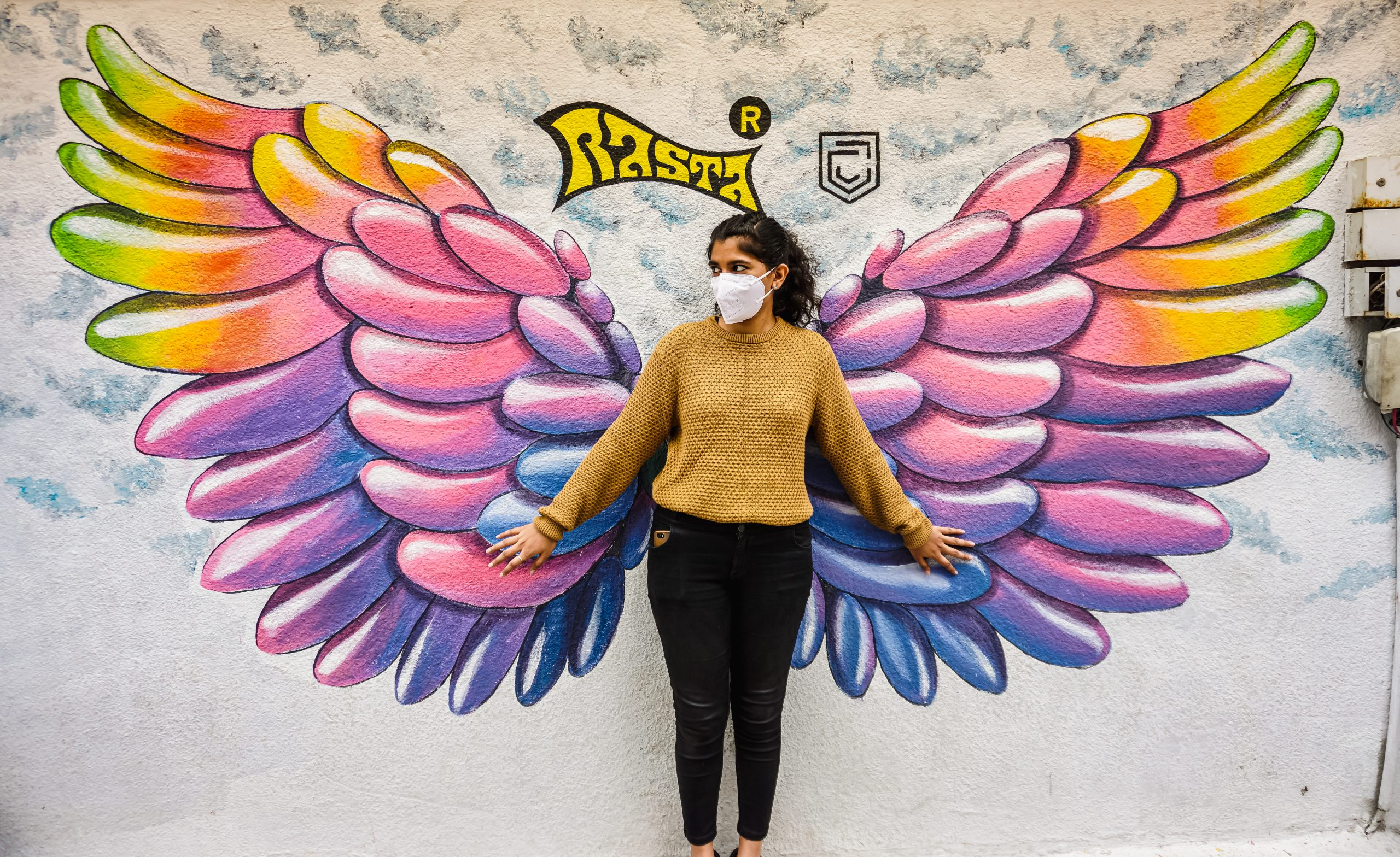 A girl standing near a painted wall