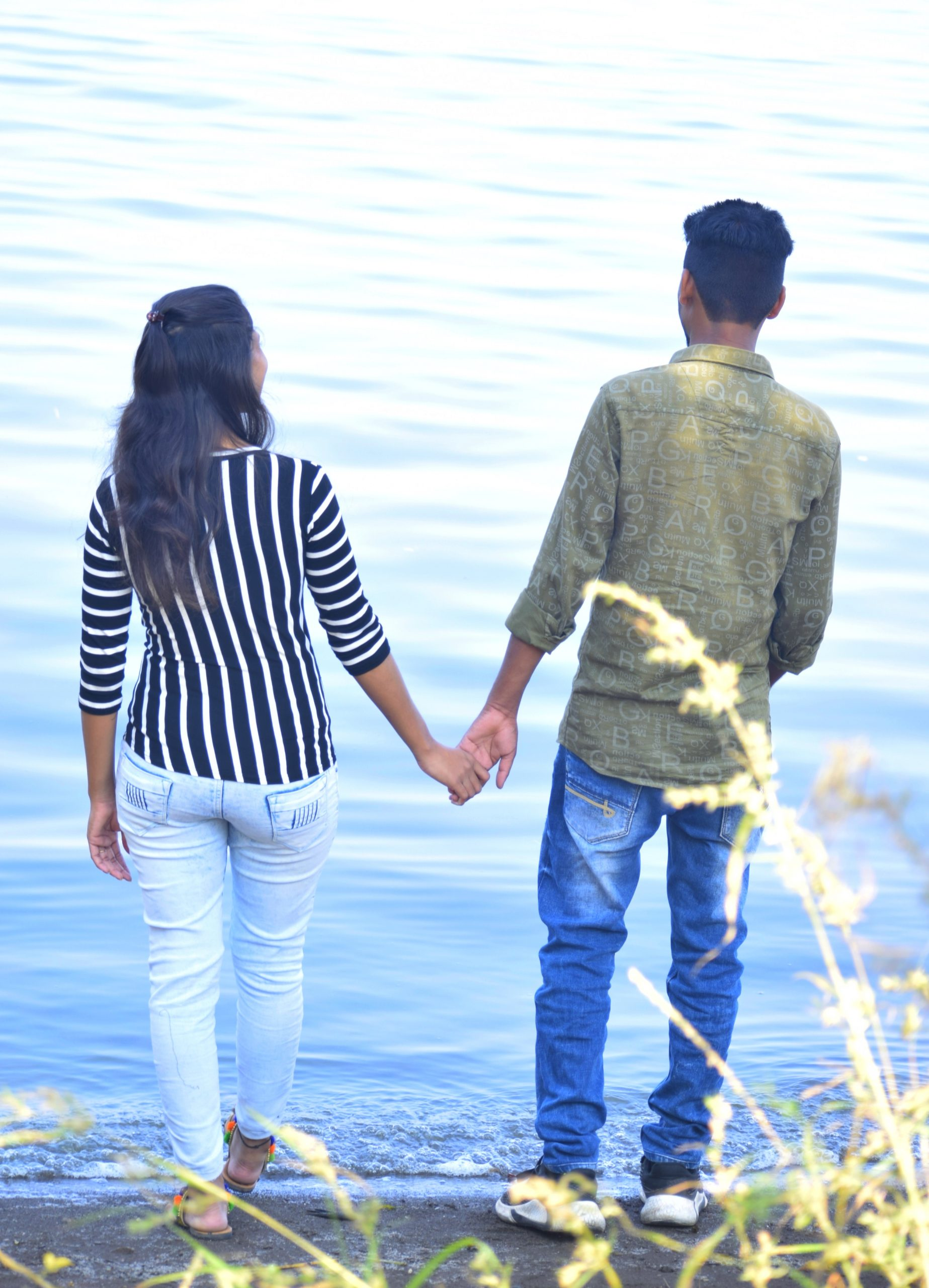 couple holding hands by the lake