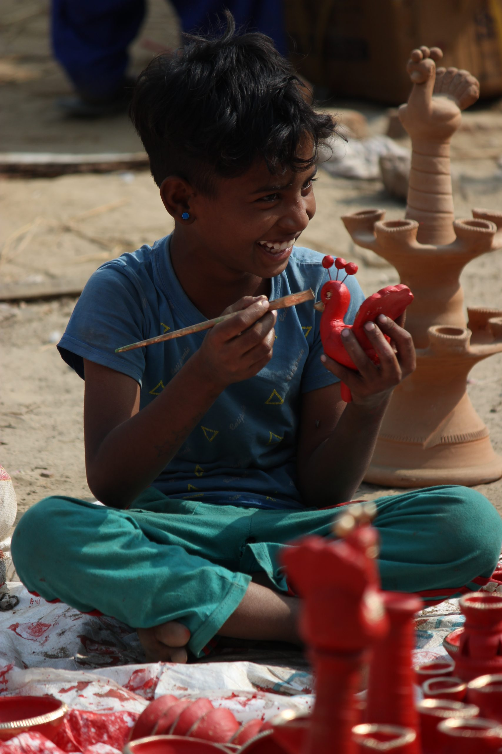 A boy painting clay items