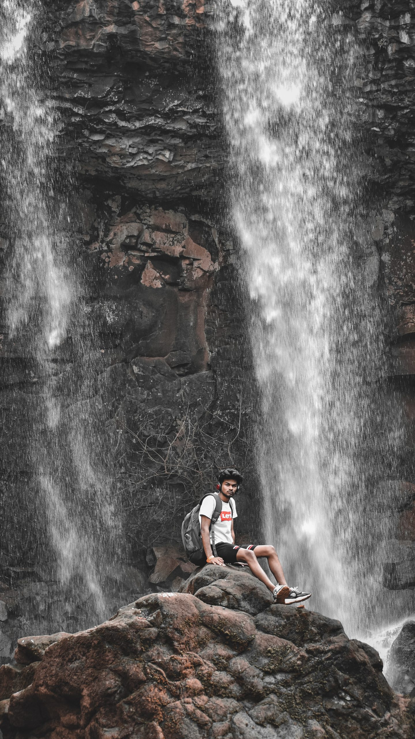 A boy under a waterfall