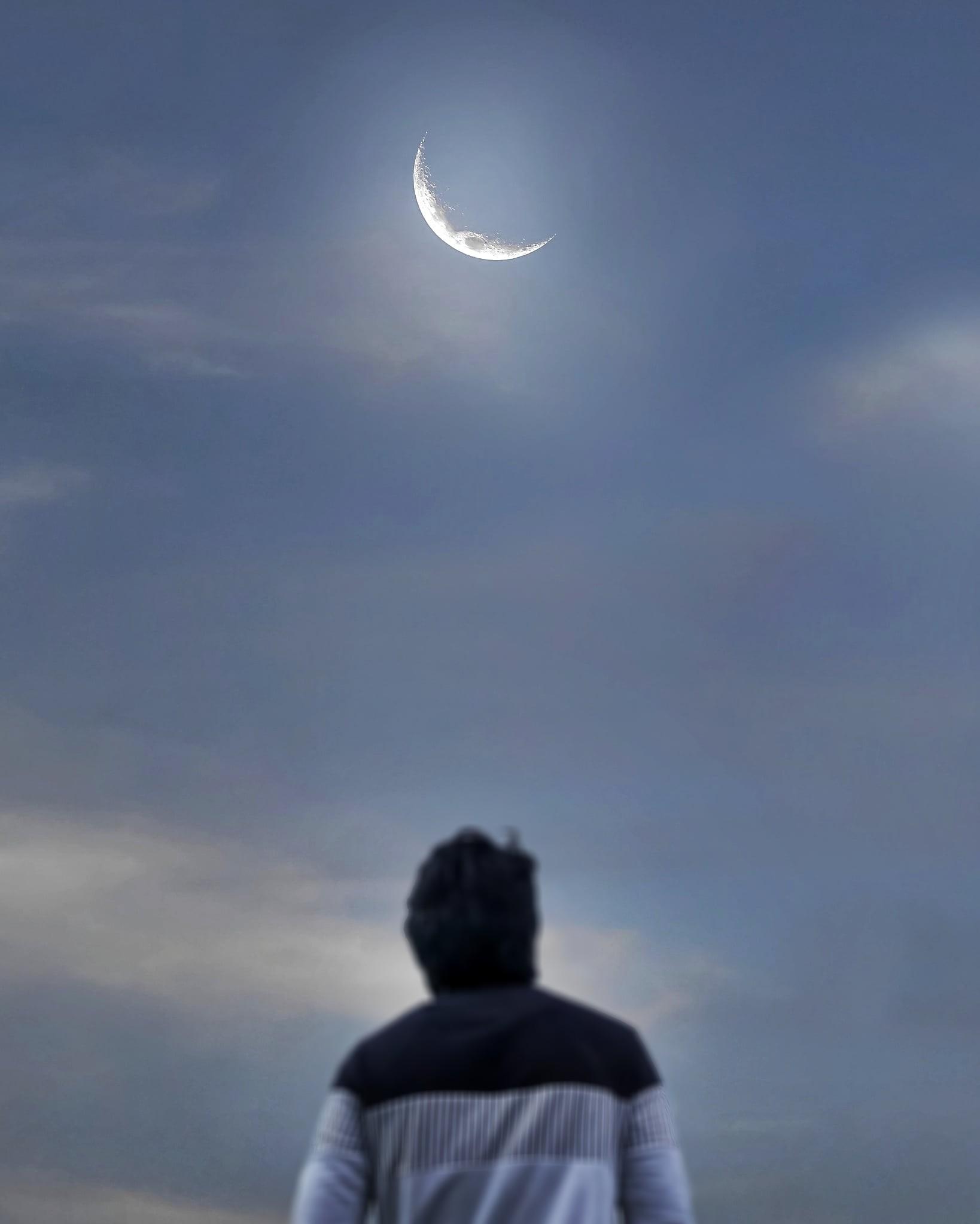 A man looking towards moon