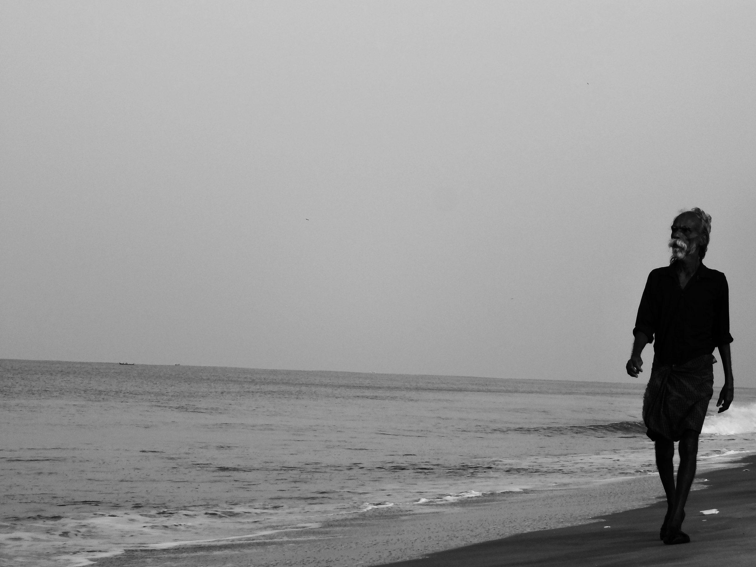 man walking on the beach side