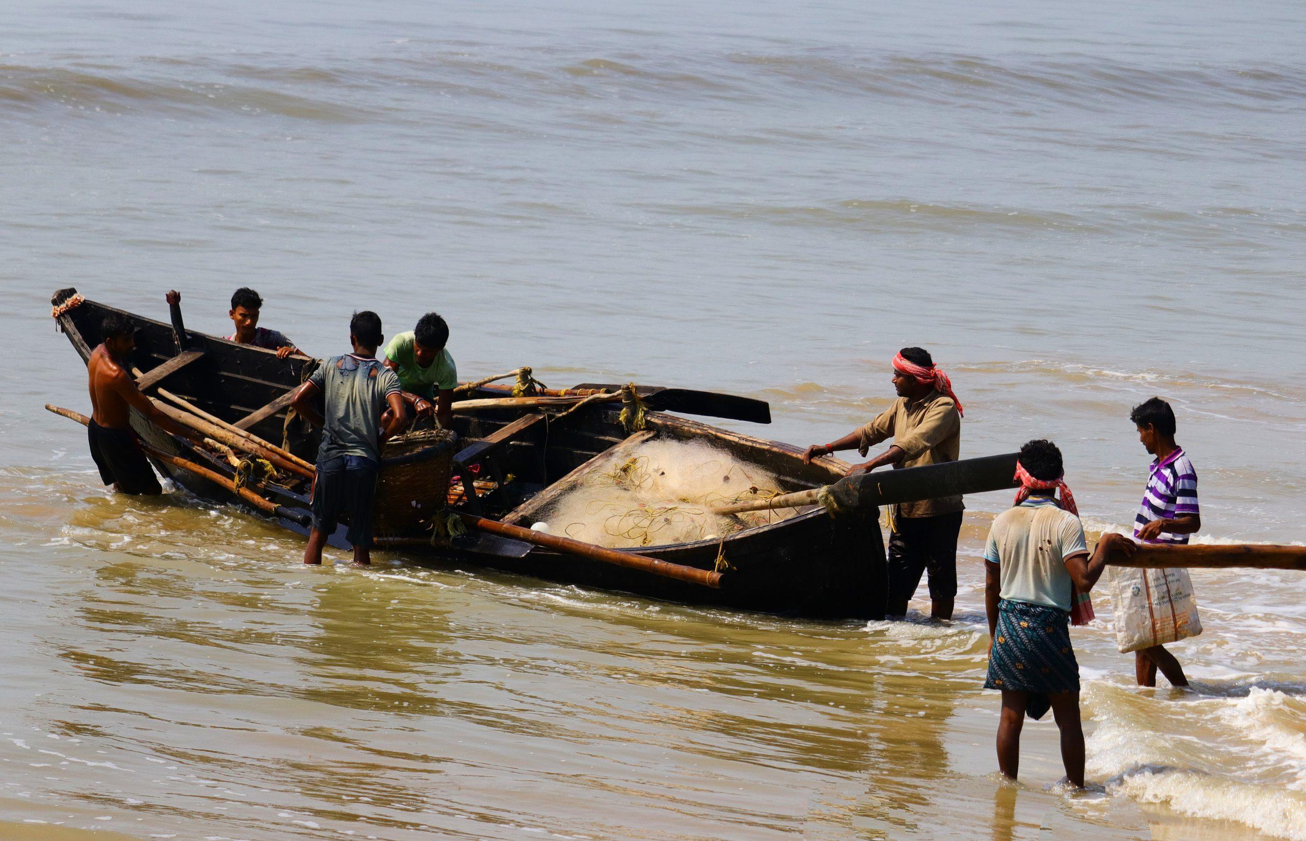 Fishermen getting their boat in water