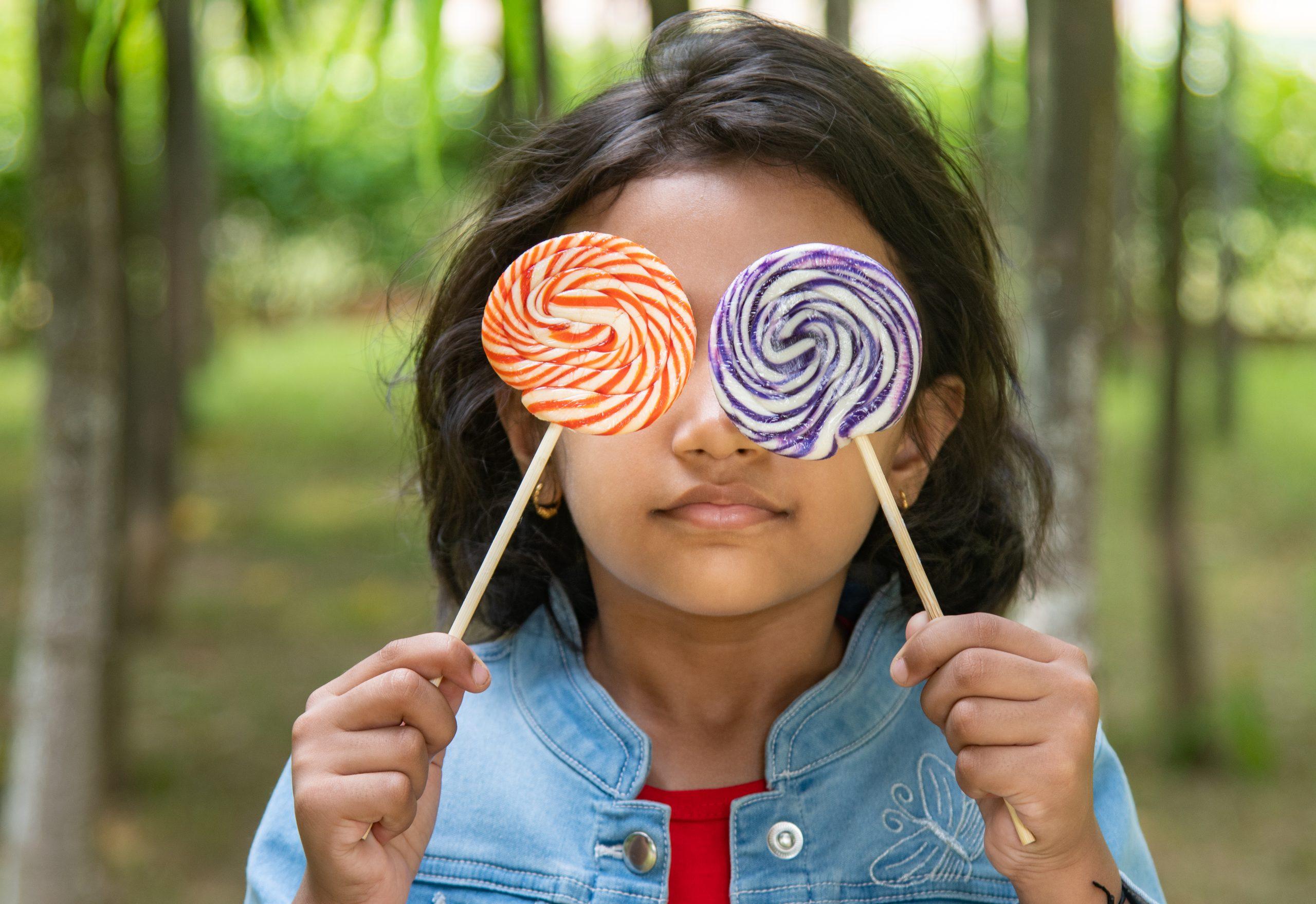 girl holding lollipops