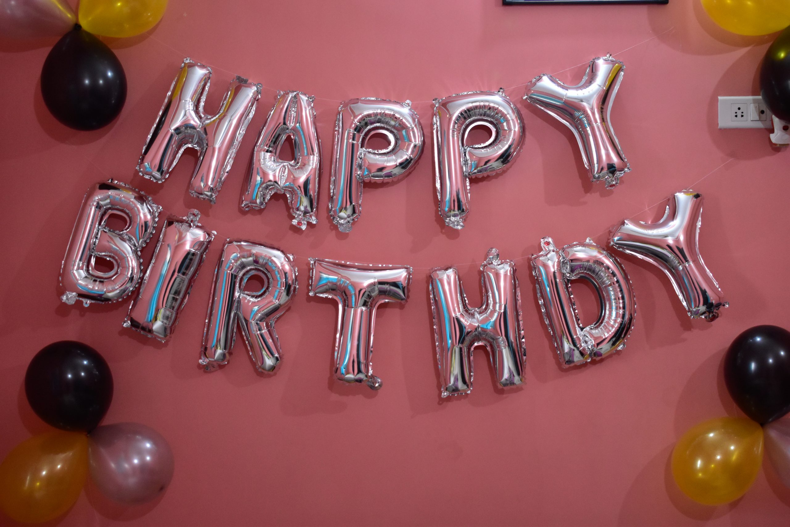 happy birthday foil balloons on the wall