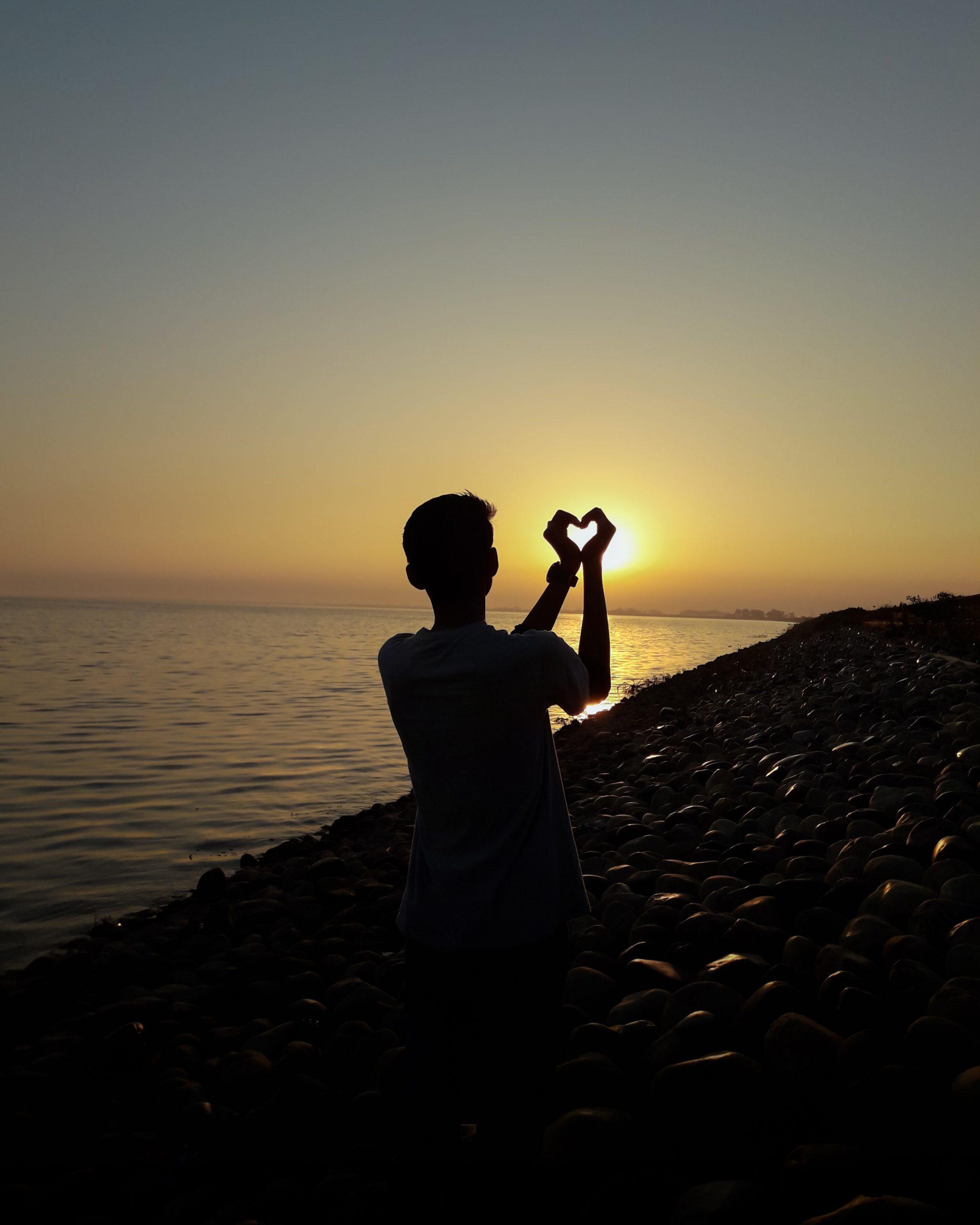 Boy make heart shape through sun