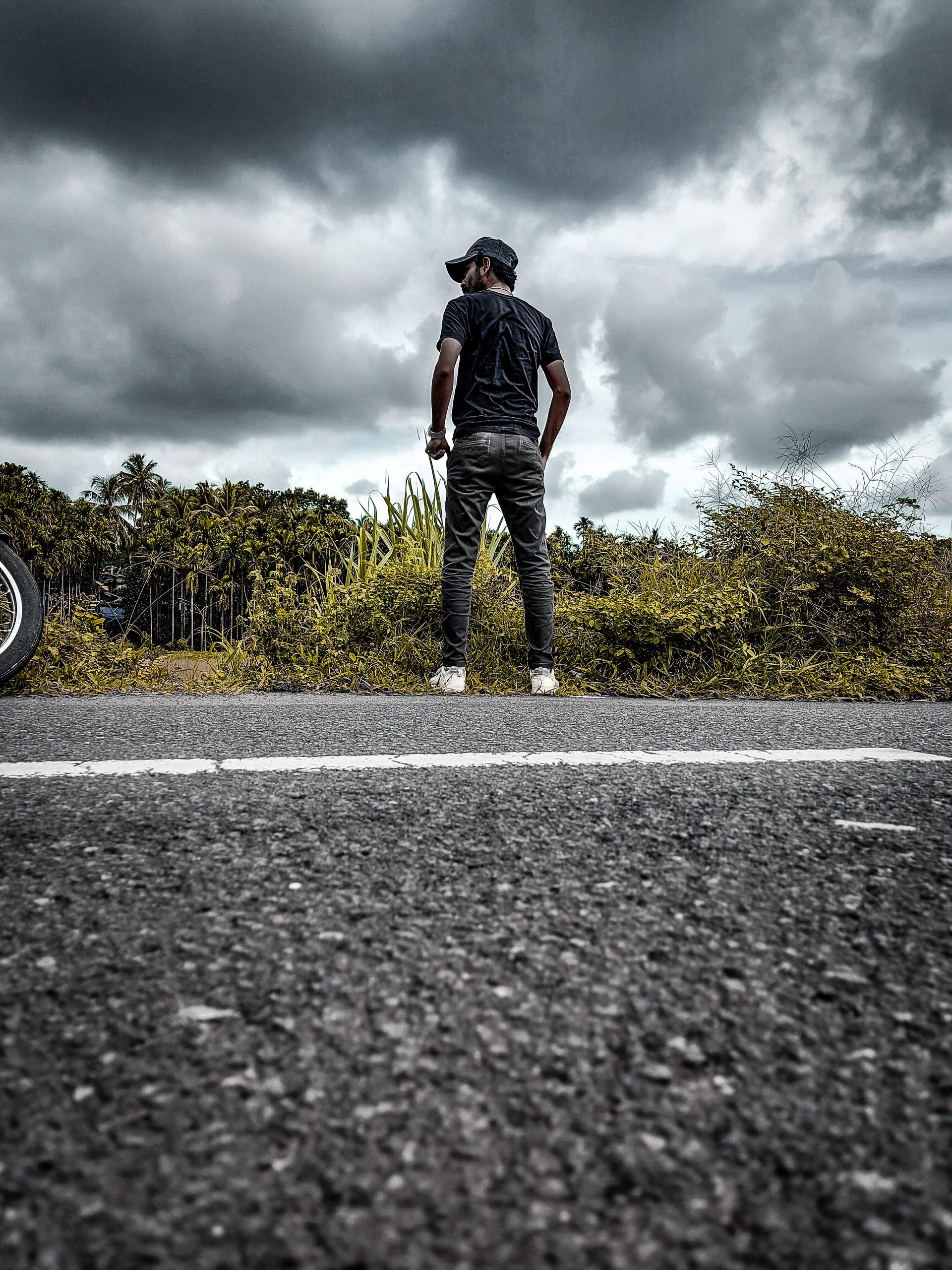 man standing on the roadside