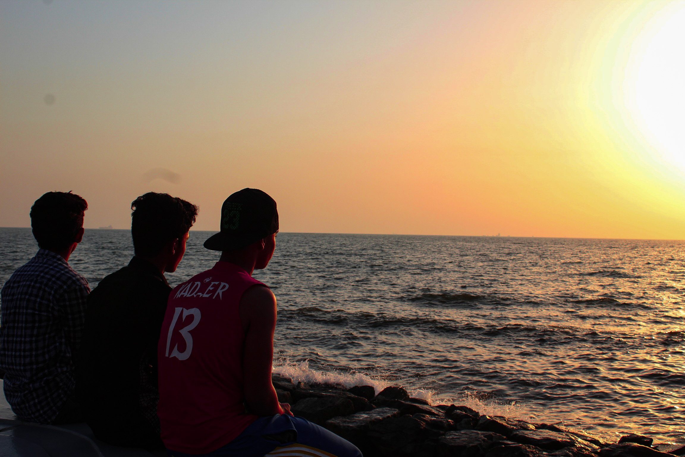 boys watching sunset at the sea