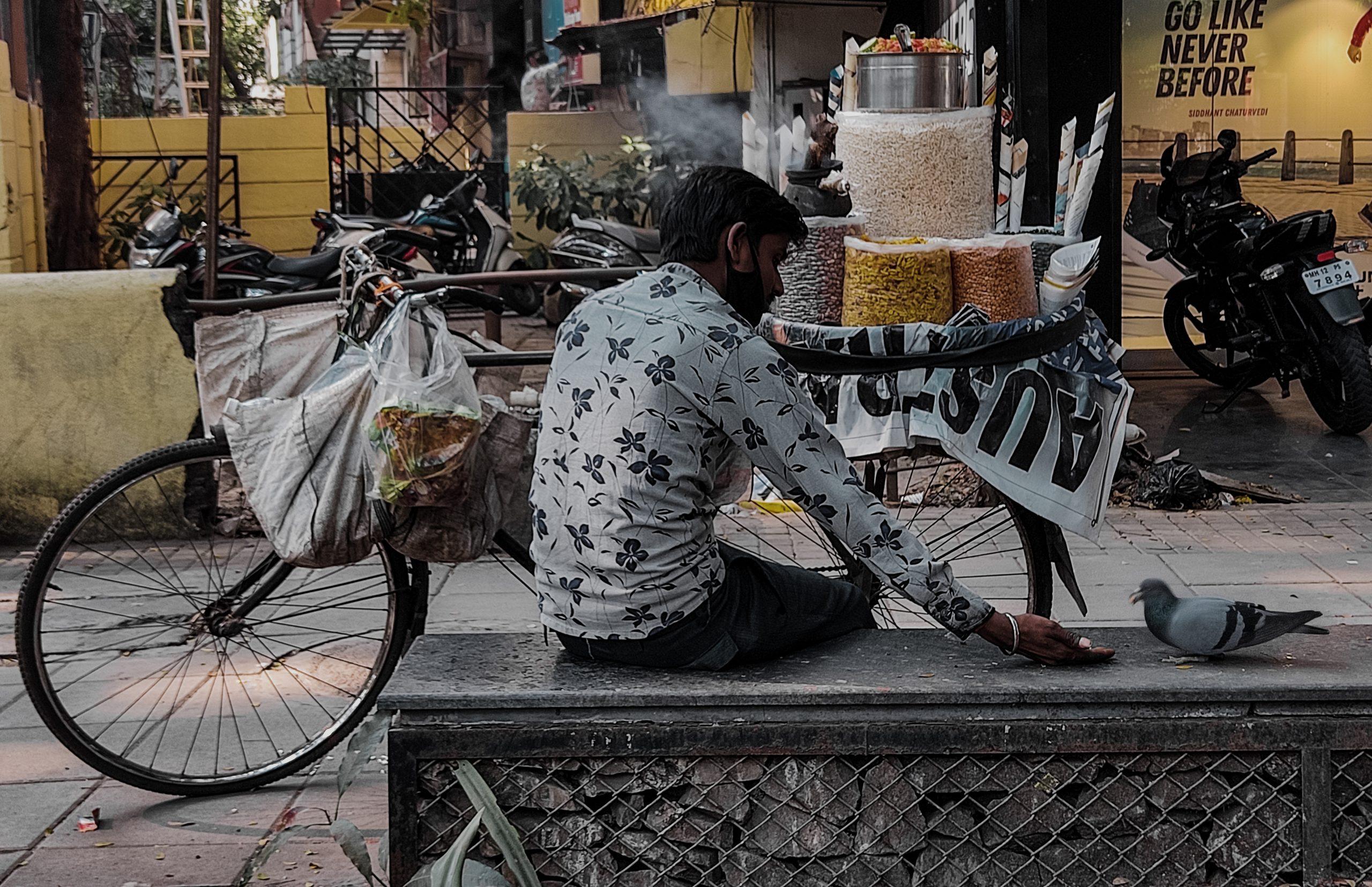 man feeding pigeon