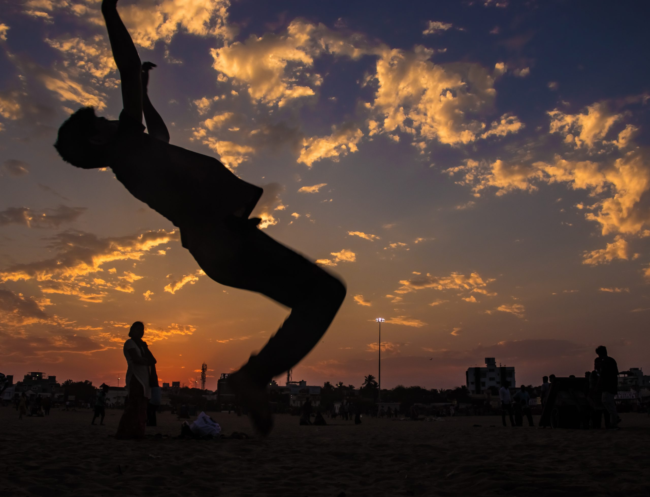 silhouette of boy flipping at the beach