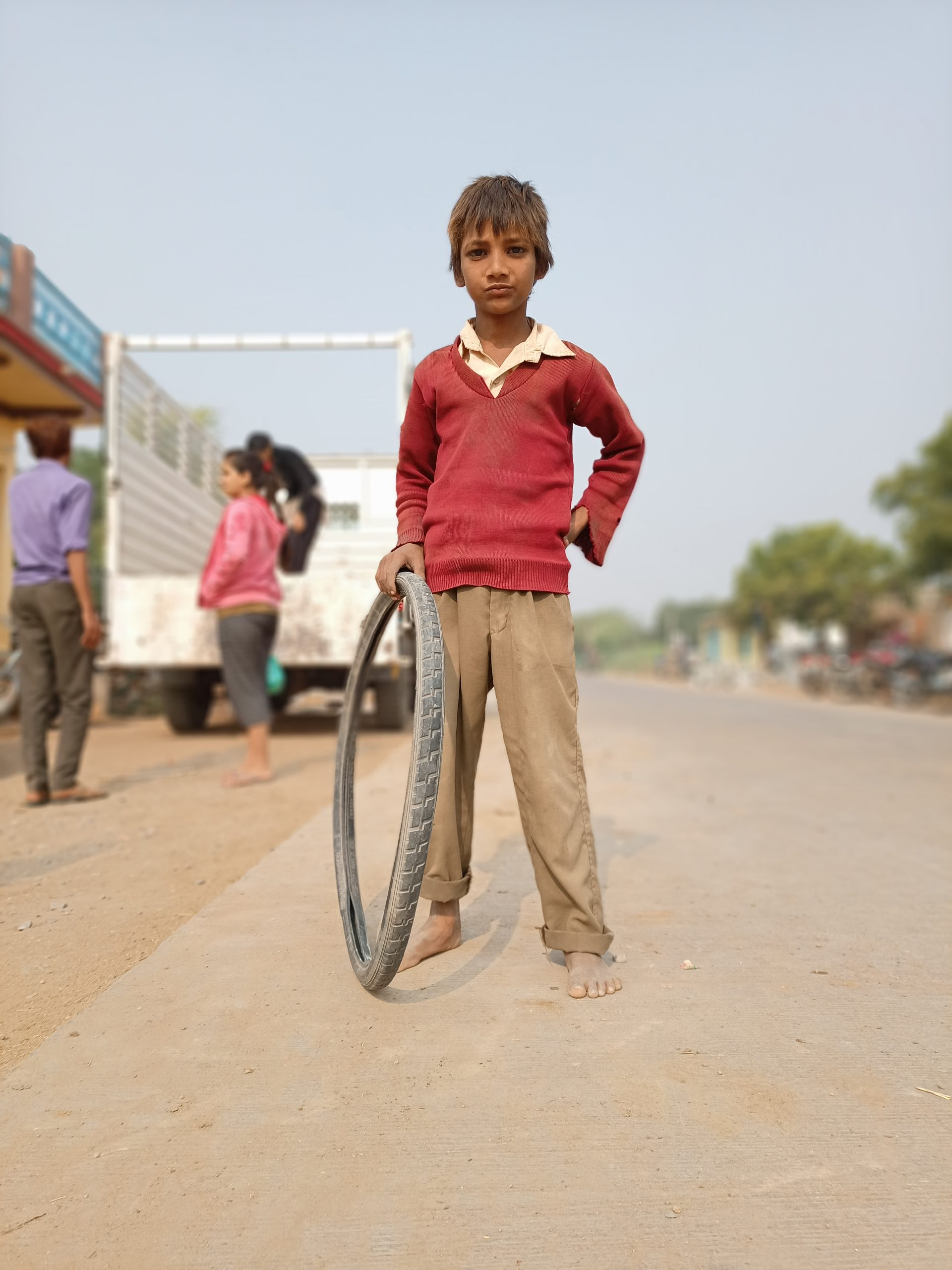 A village boy playing with bicycle tire