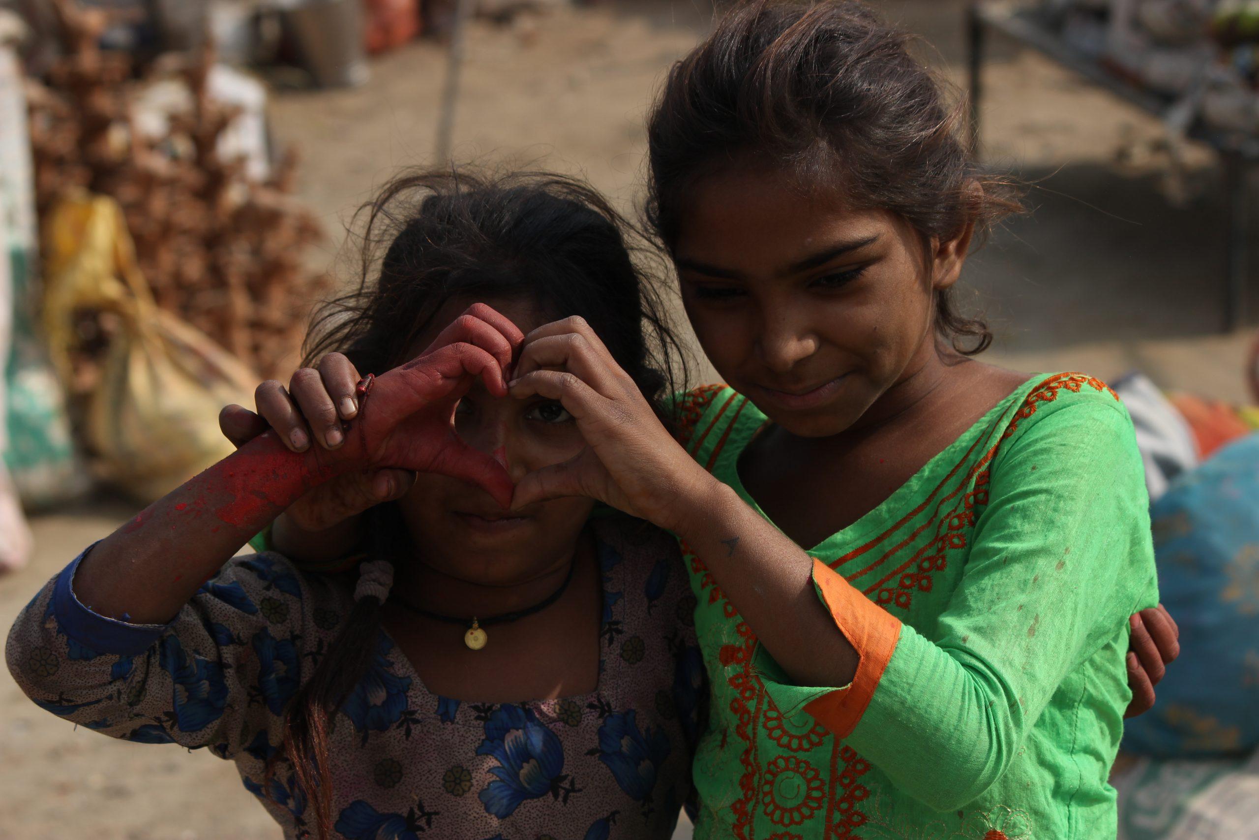 Little girls make heart shape with hands