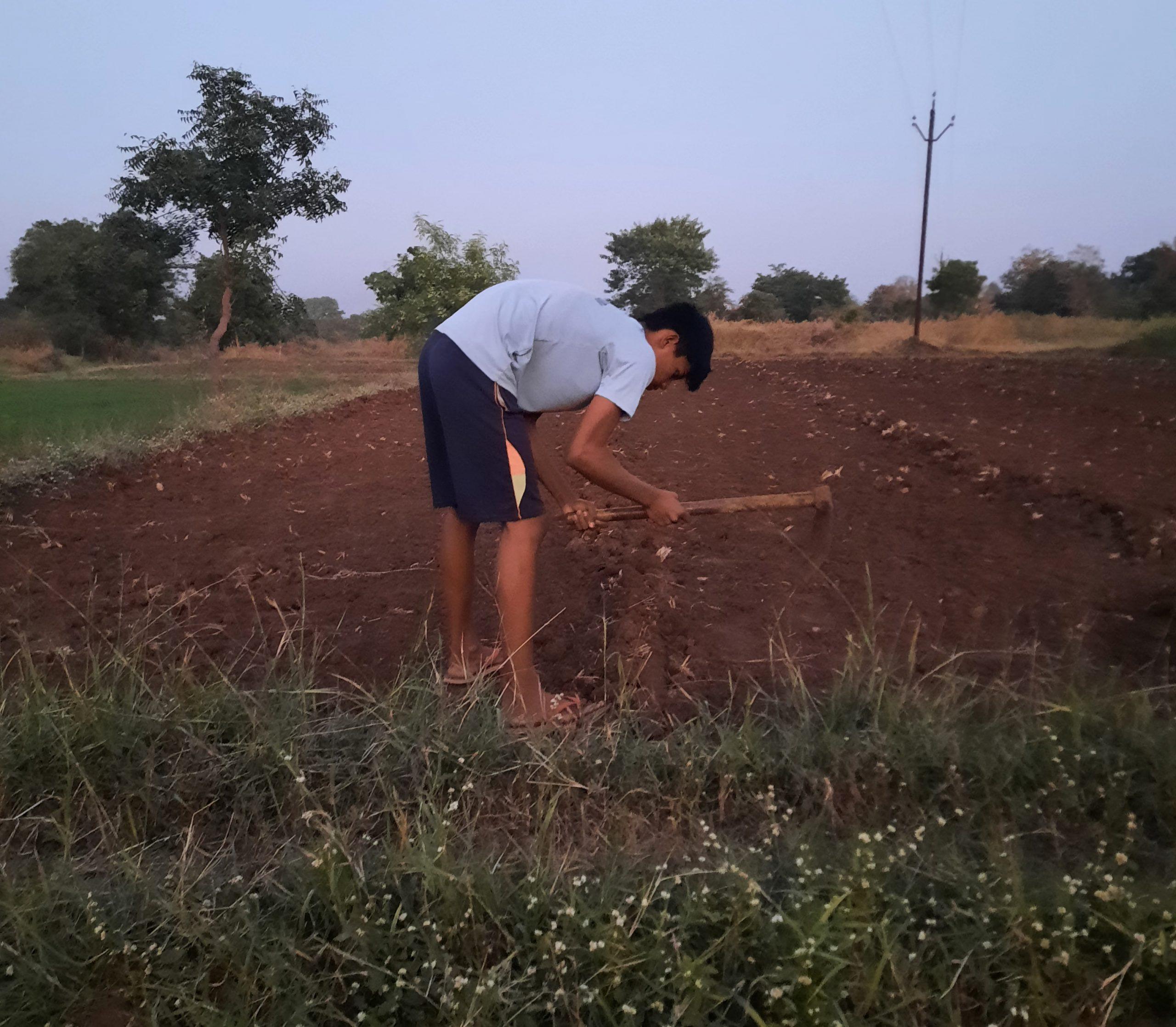 A boy working in a field