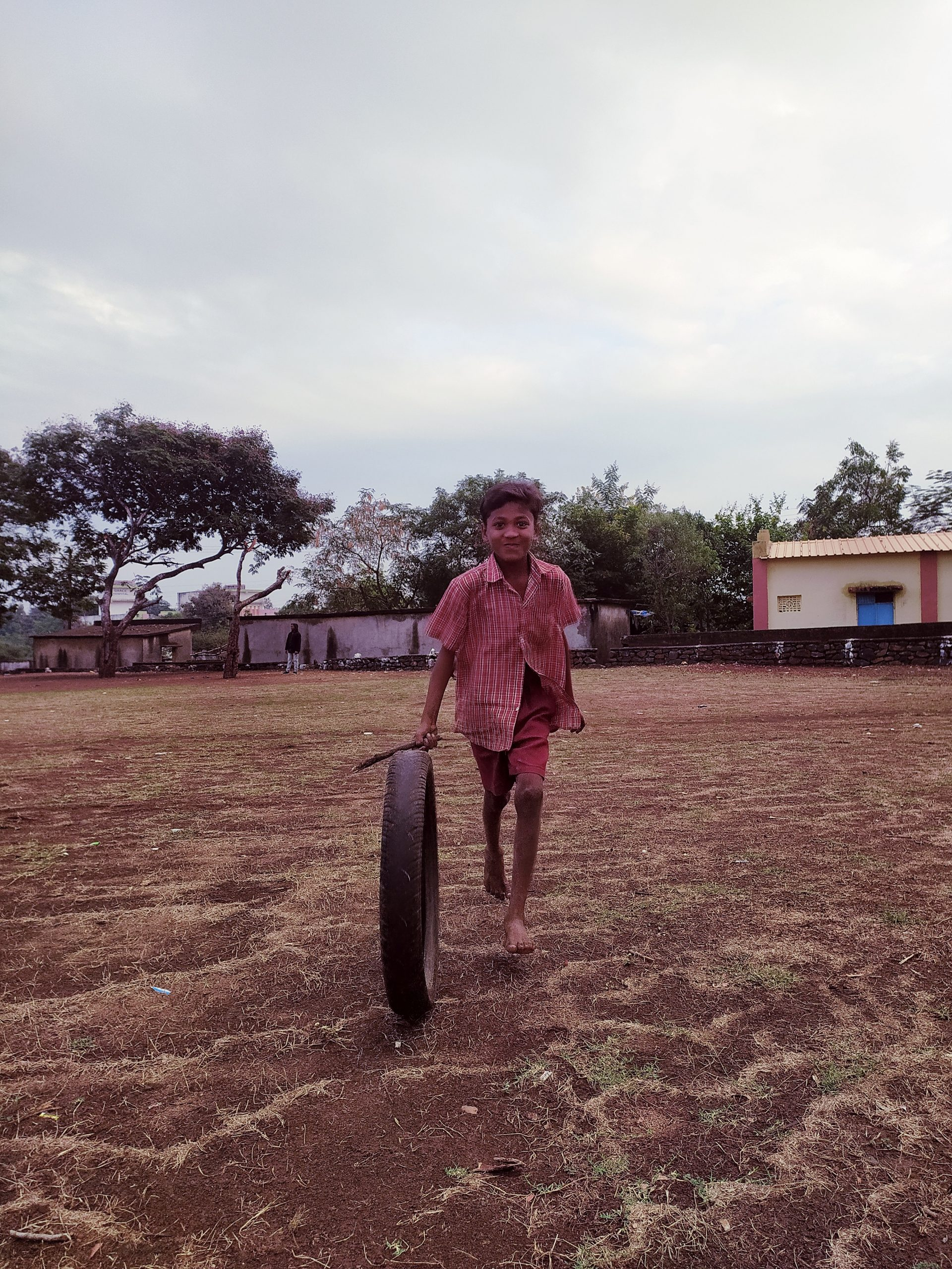 A village child playing with a tire