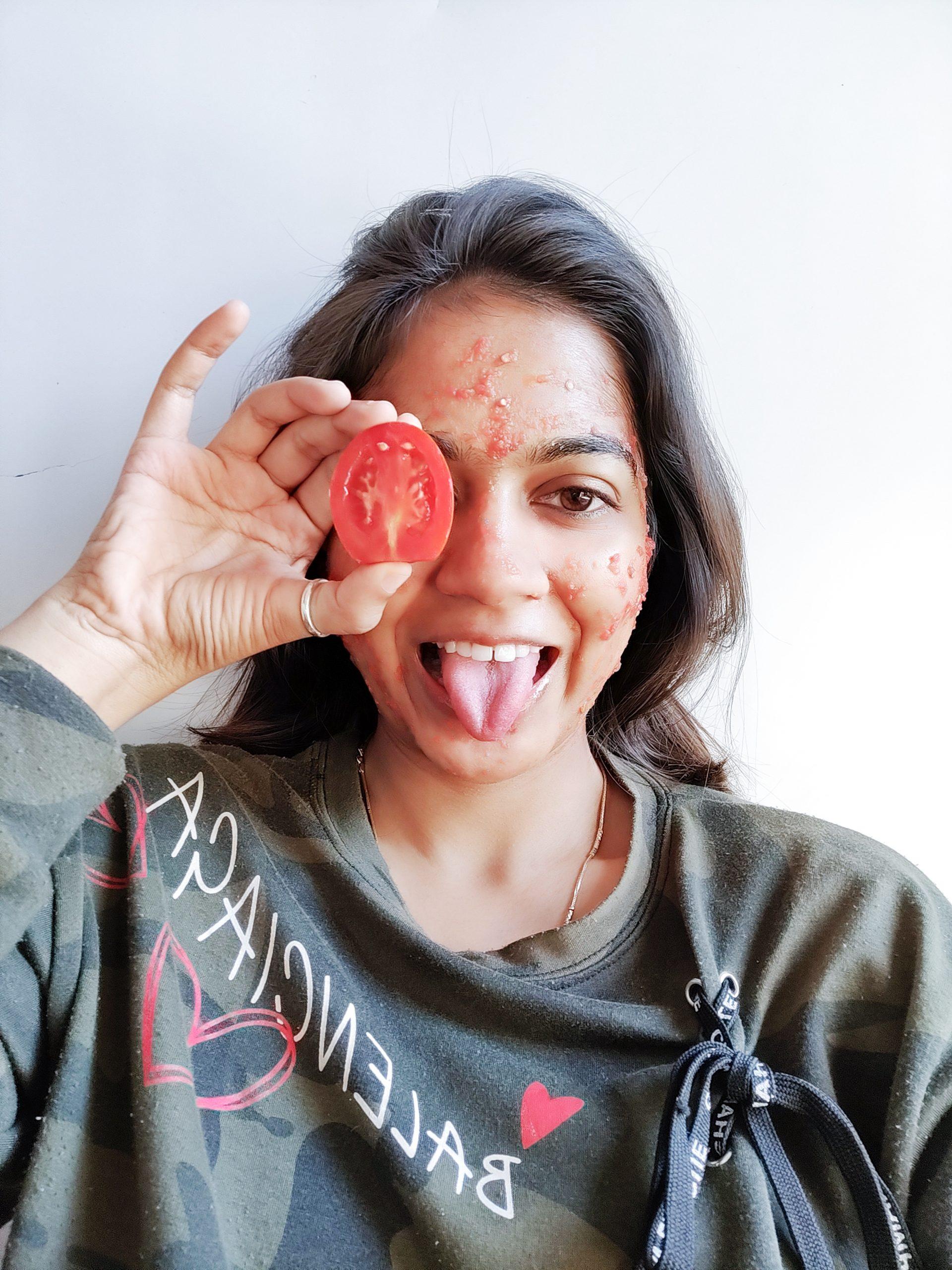 A girl applying tomato face mask