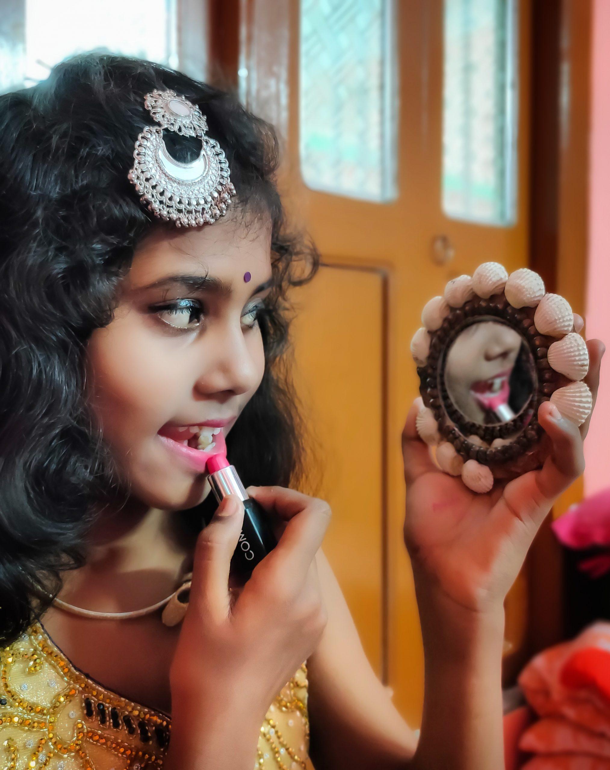 A girl using lipstick