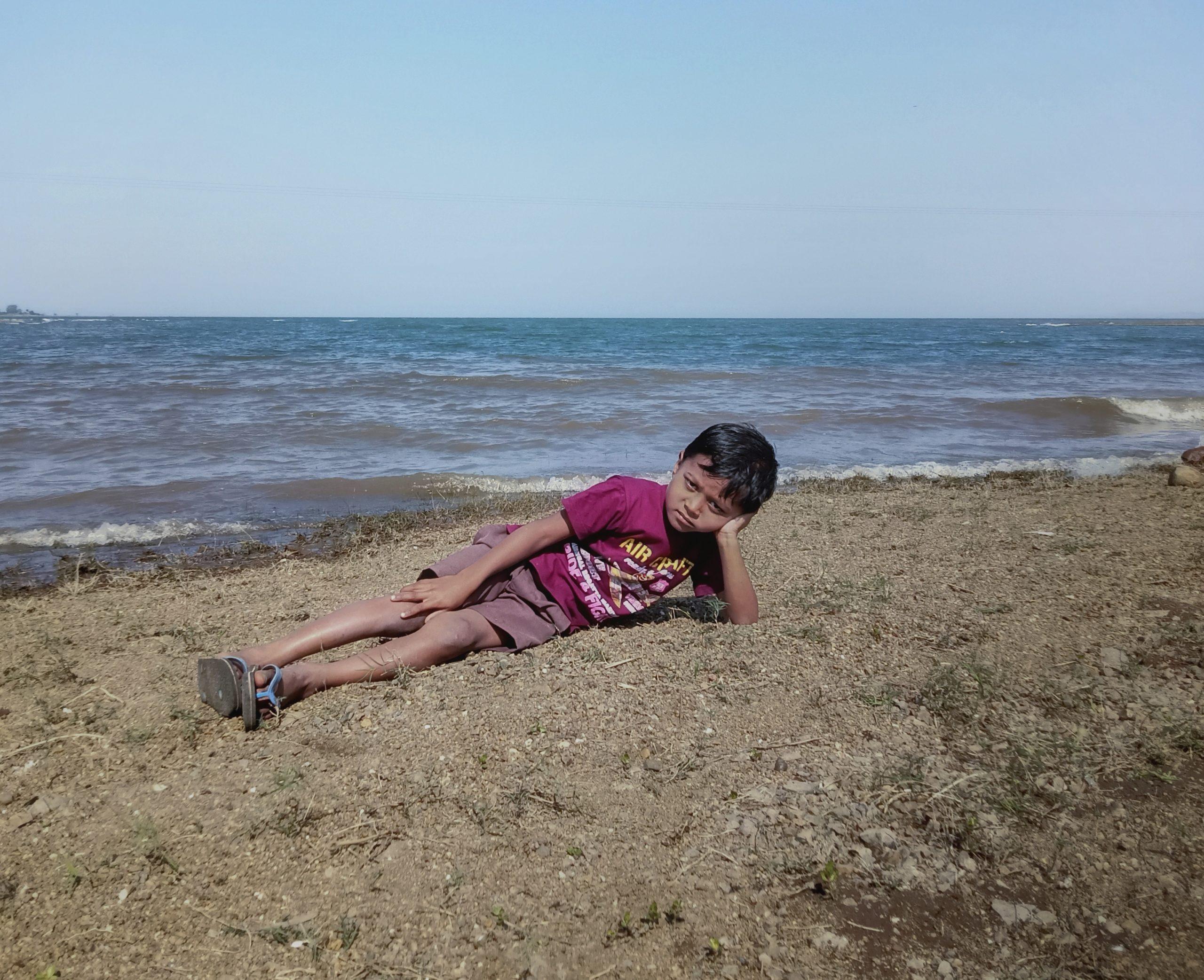 A little boy relaxing on a beach
