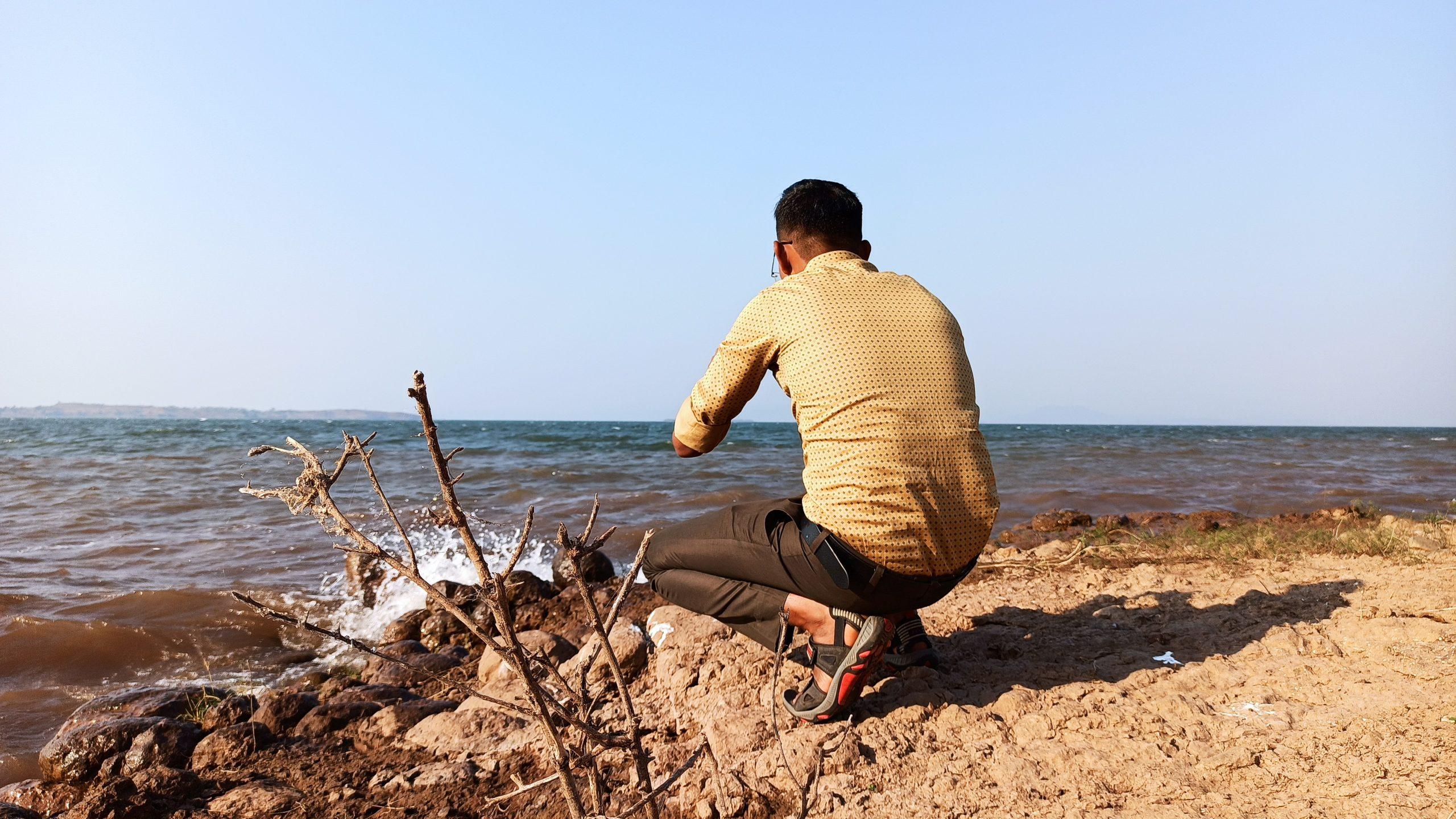 Man Capturing beautiful beach scene in camera