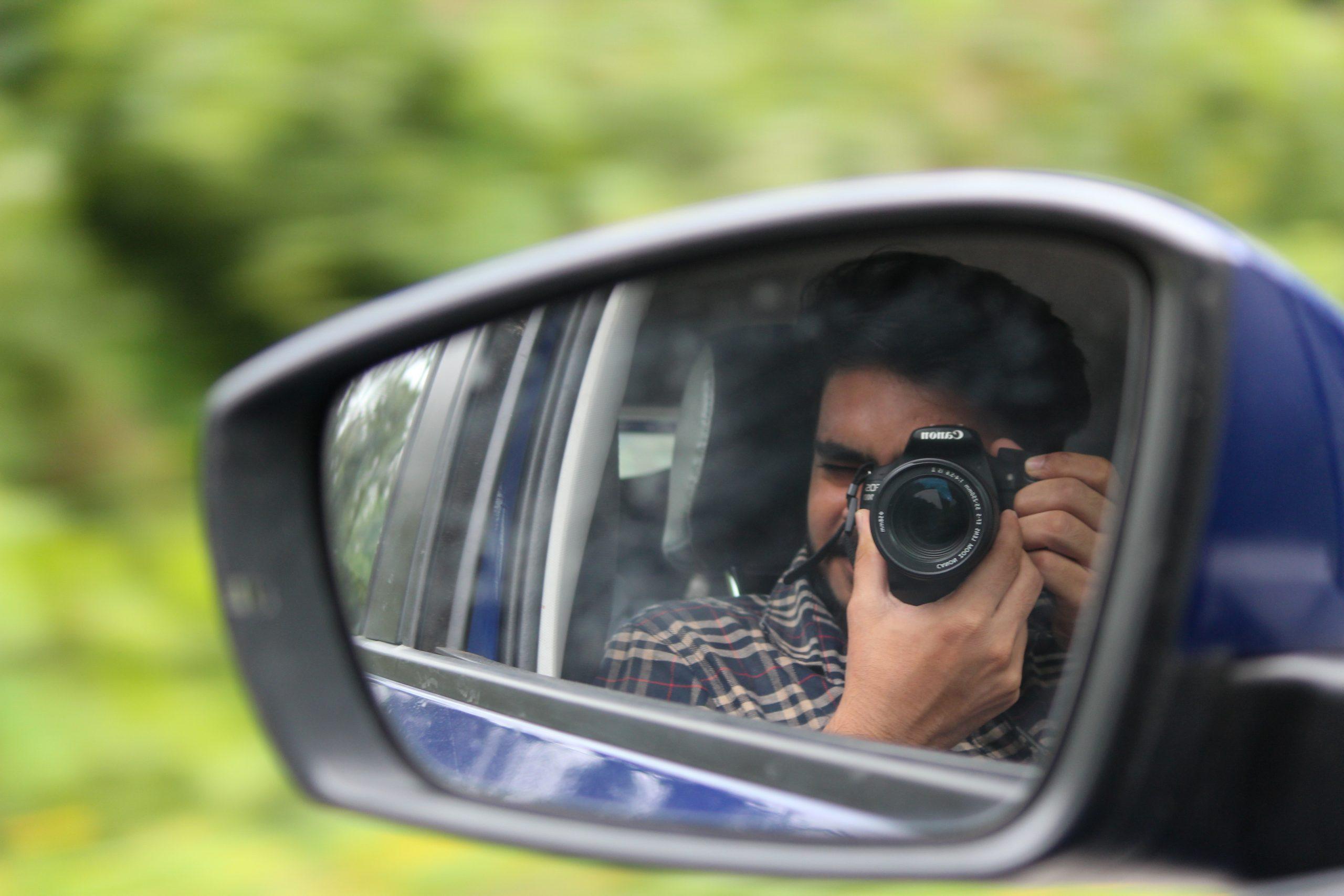 A photographer capturing through back mirror