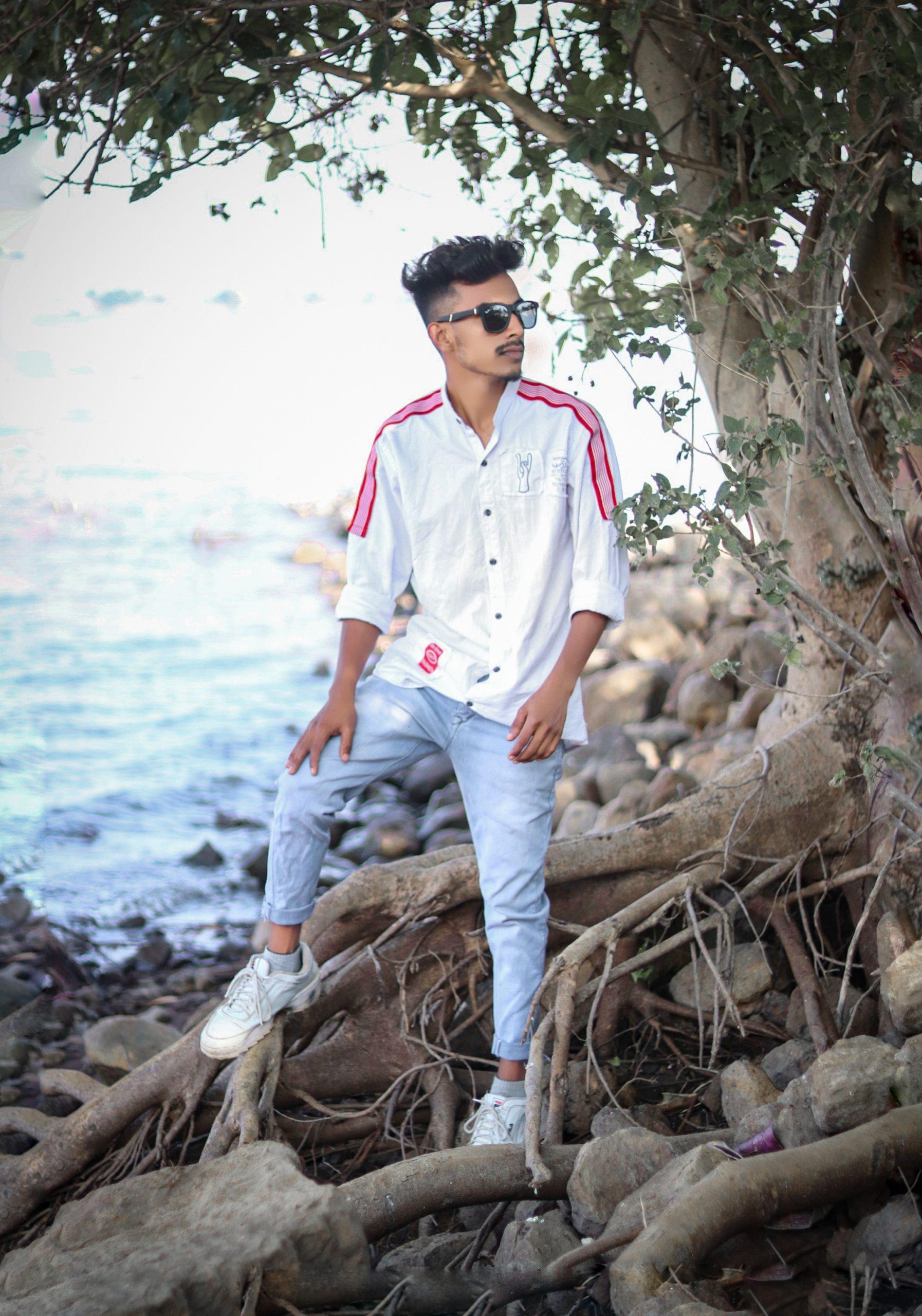A stylish boy on a tree roots