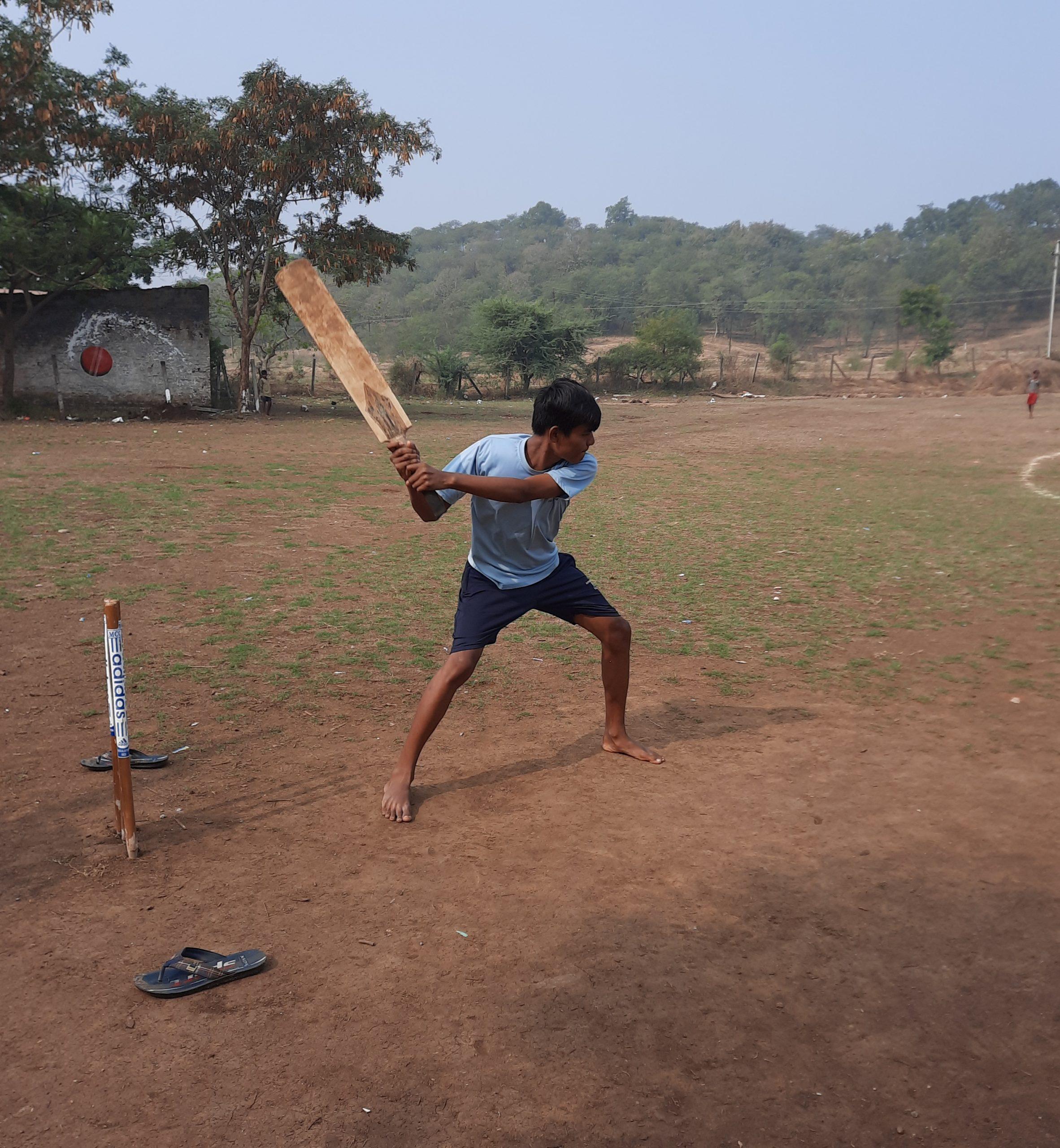 A boy playing cricket