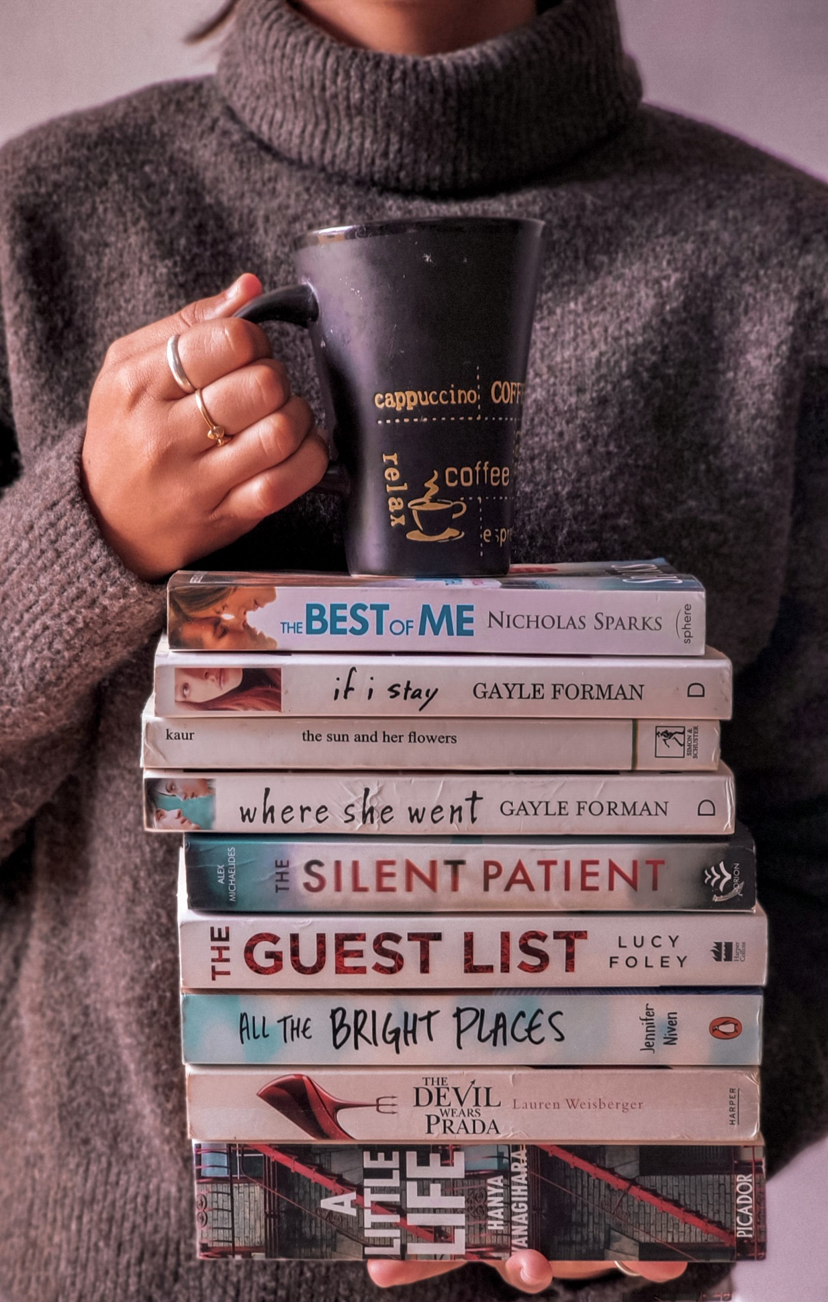 books and coffee mug in hand