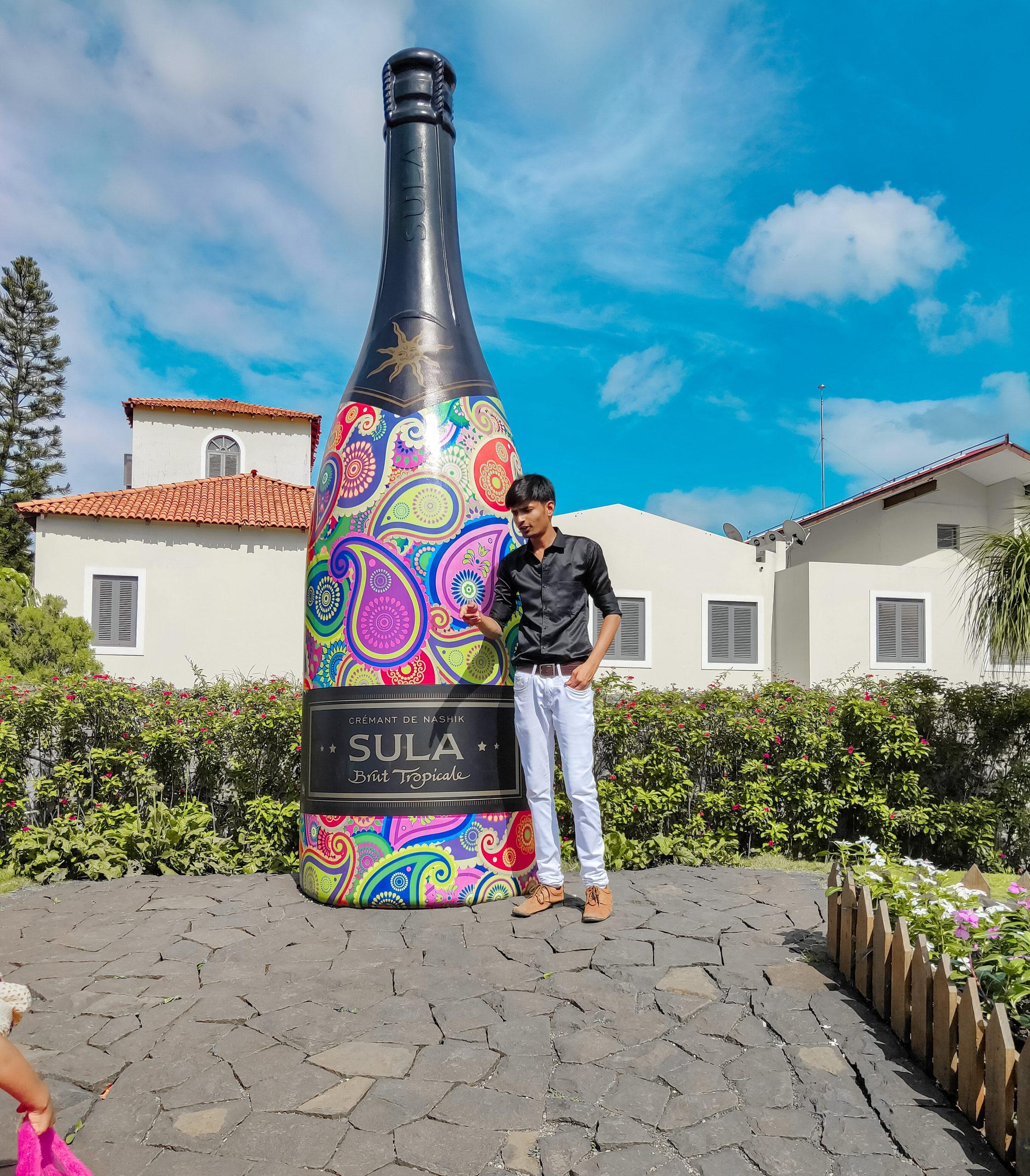 Boy posing in front of artificial bottle