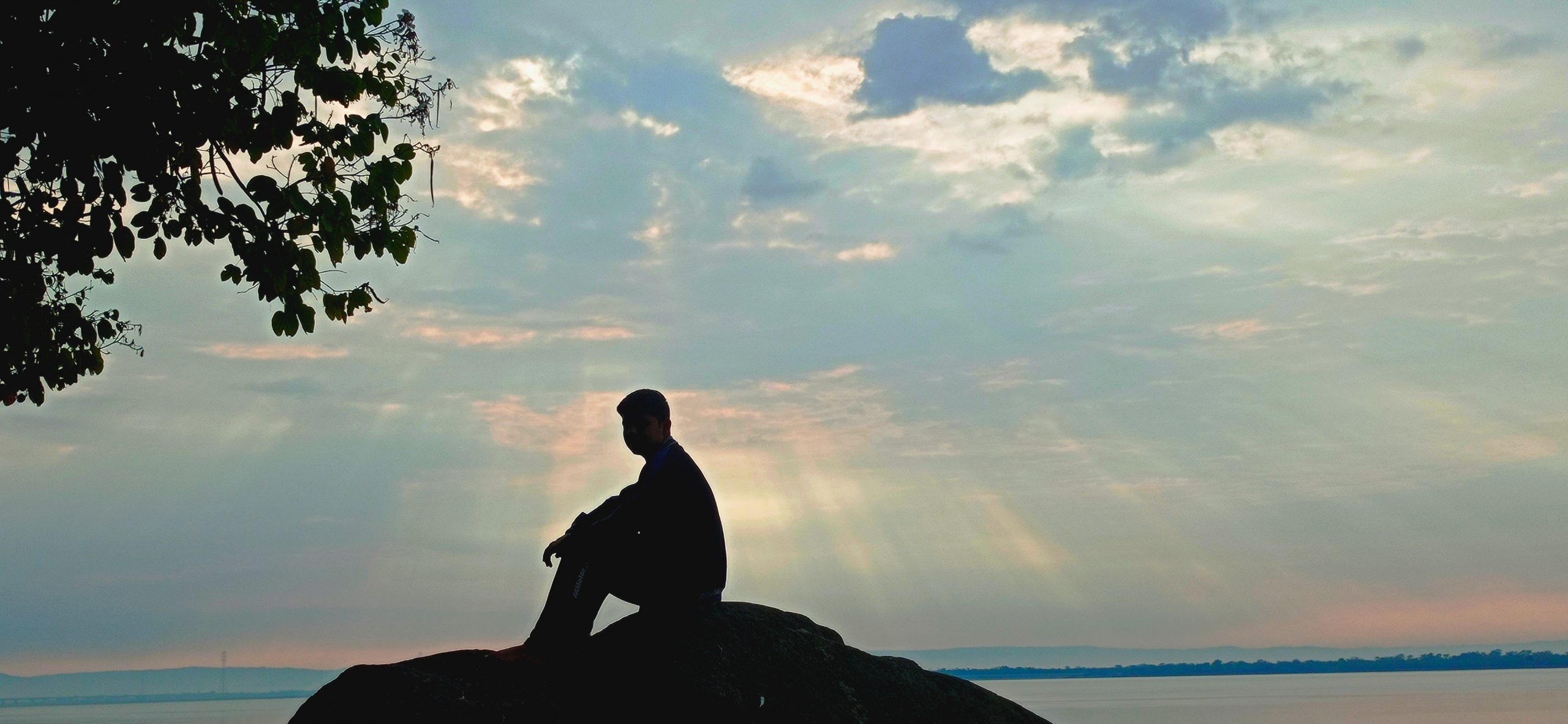 silhouette of man sitting on a rock