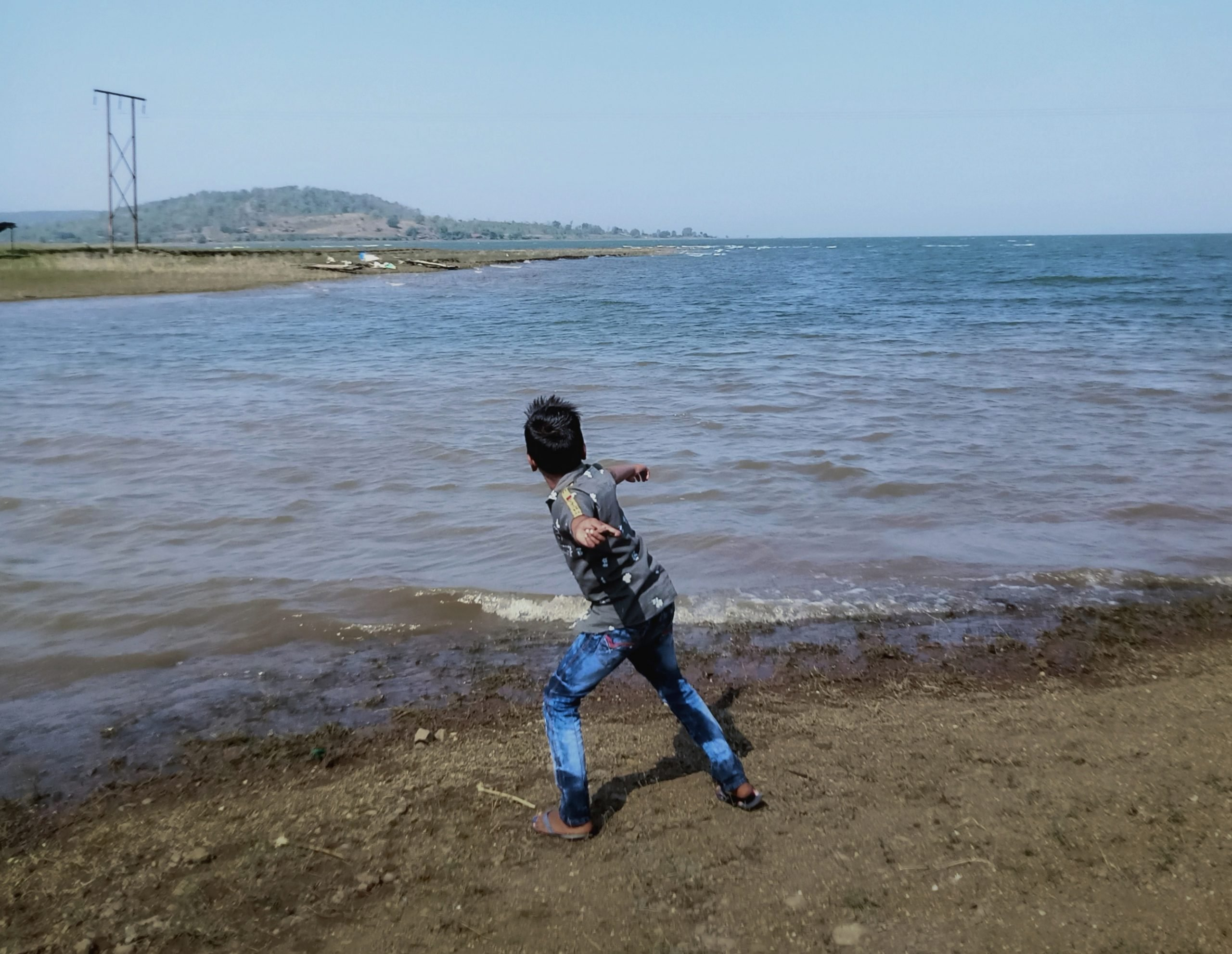 Boy throwing stone in water