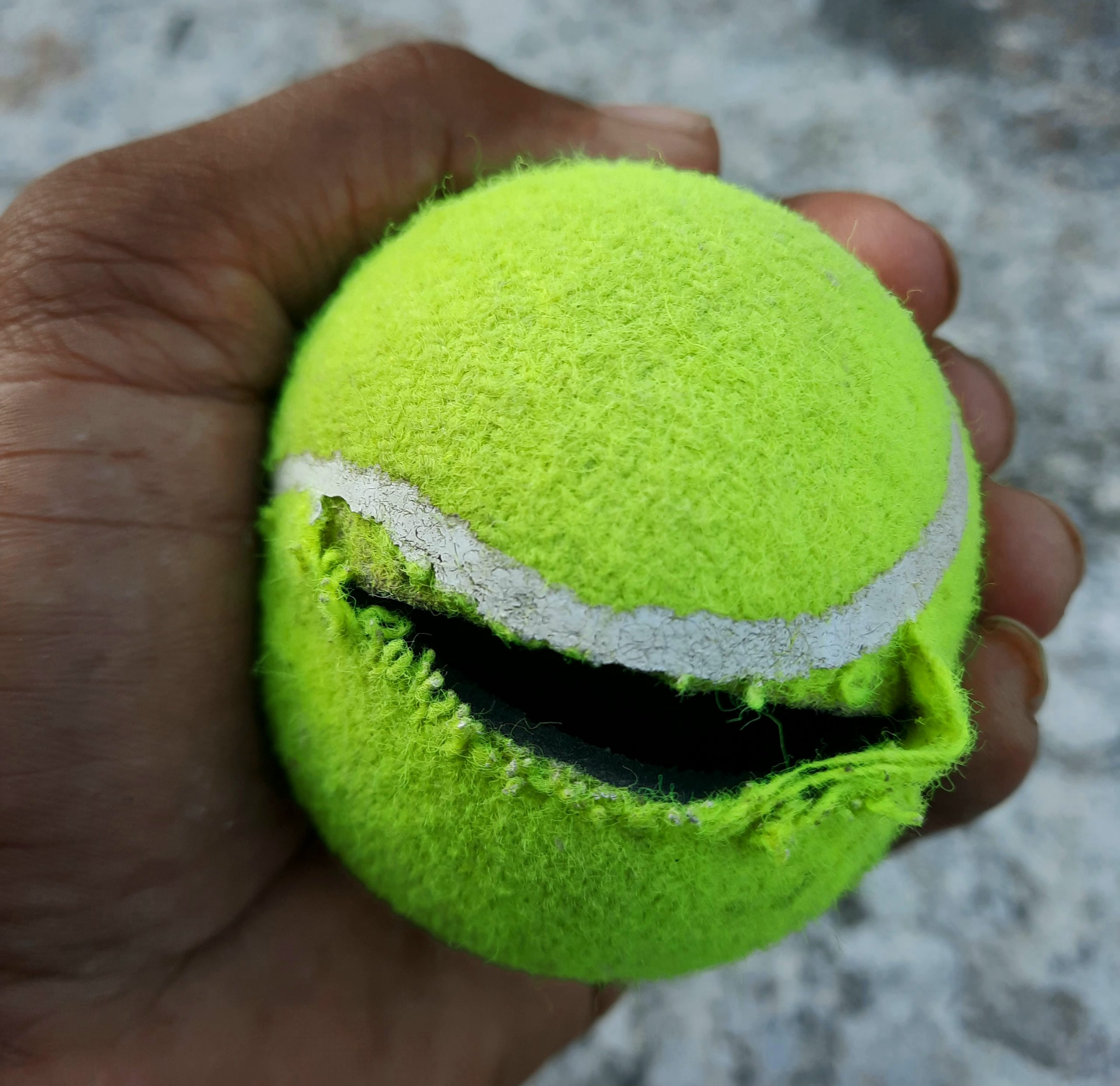 torn tennis ball in hand