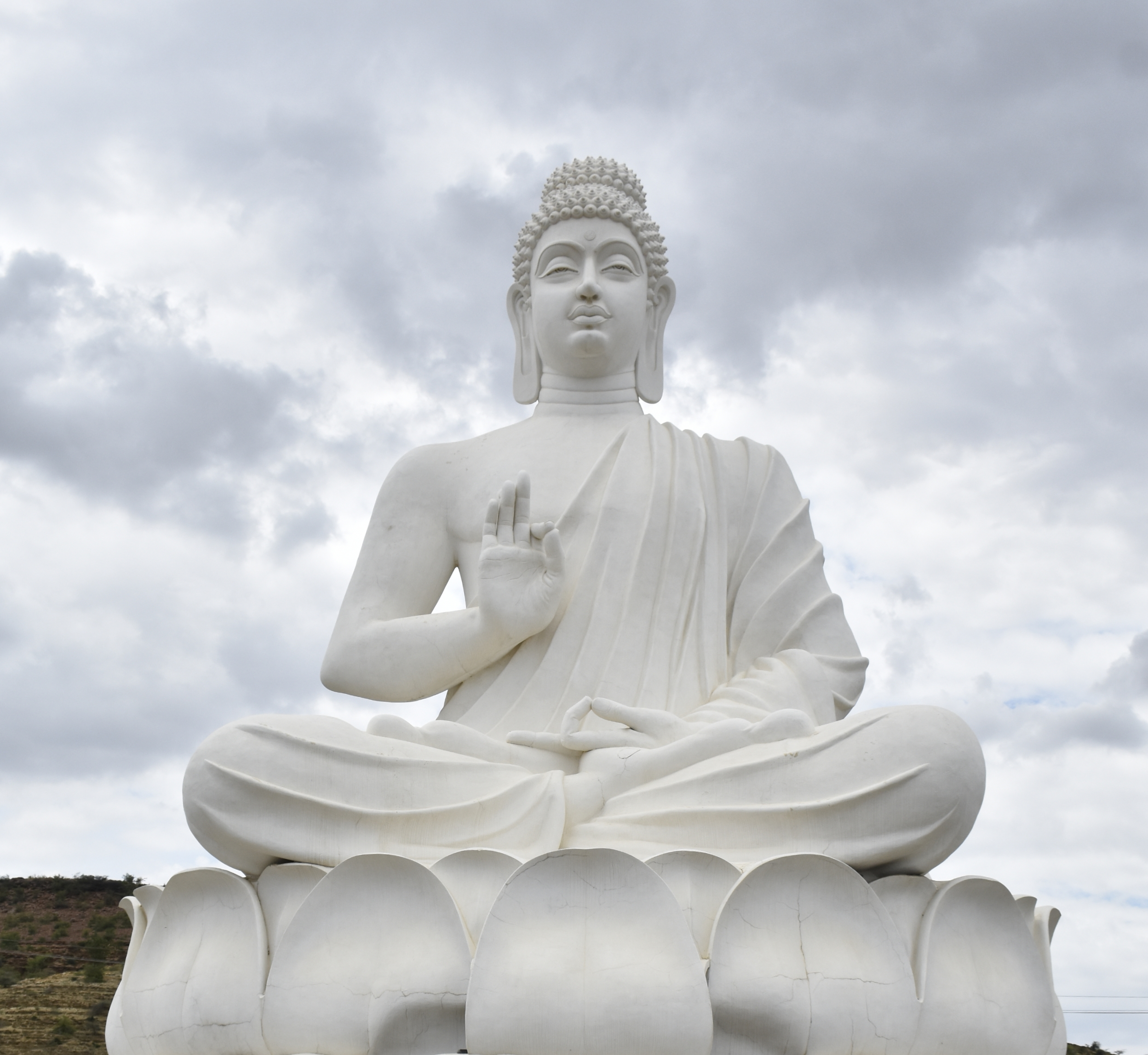 Buddha statue under cloudy sky